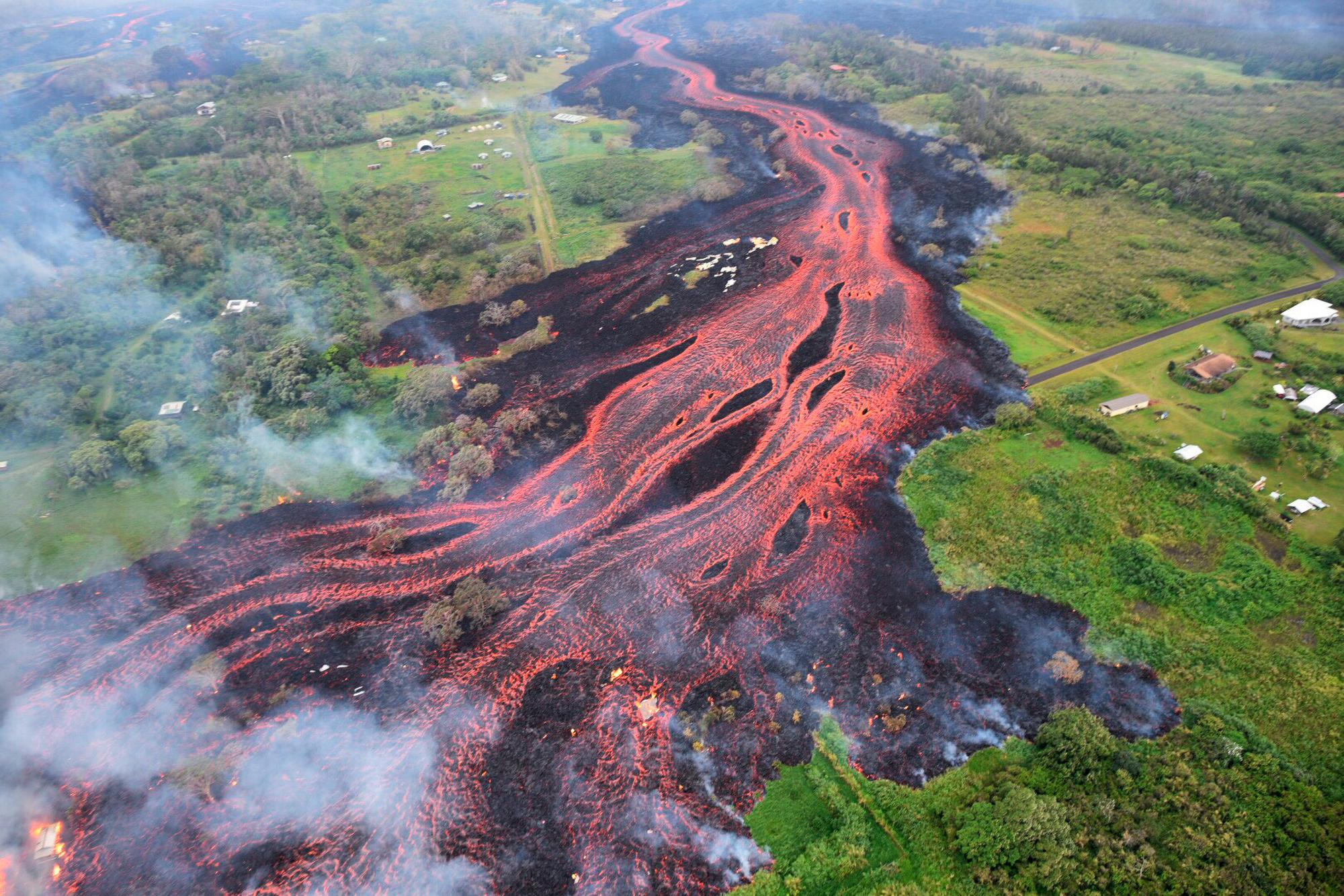 FILE - In this May 19, 2018 aerial file photo released by the U.S. Geological Survey, lava flows from fissures near Pahoa, Hawaii. White plumes of acid and extremely fine shards of glass billowed into the sky over Hawaii as molten rock from Kilauea volcano poured into the ocean, creating yet another hazard from an eruption that began more than two weeks ago: A toxic steam cloud. (U.S. Geological Survey via AP, file)