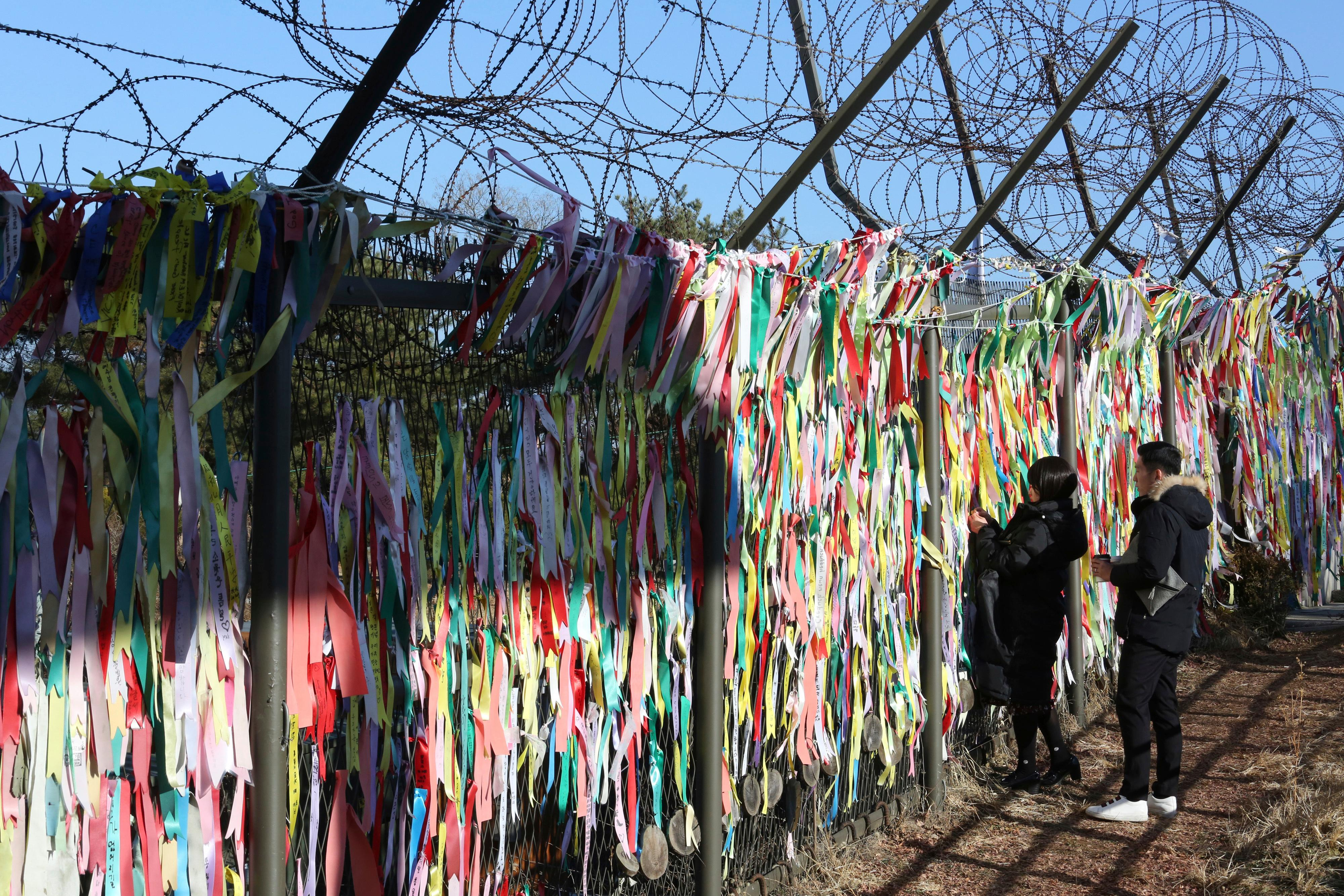 "A woman hangs a ribbon wishing for reunification of the two Koreas on the wire fence at the Imjingak Pavilion in Paju, South Korea, near the border with North Korea Monday, Dec. 25, 2017. North Korea on Sunday called the latest U.N. sanctions to target the country ""an act of war"" that violates its sovereignty, and said it is a ""pipe dream"" for the United States to think it will give up its nuclear weapons. (AP Photo/Ahn Young-joon)"