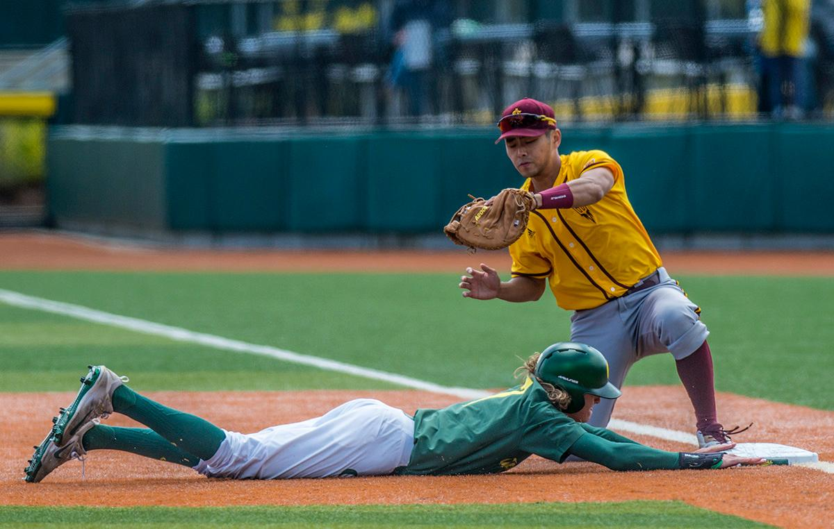 Oregon Ducks Matthew Dyer (#7) slides back to first base as Arizona State Sun Devils first baseman Lyle Lin (#27) attempts to get him out. The Oregon Ducks defeated the Arizona State Sun Devils 3-2 on Sunday in the final game of the three-game series to close out with two wins and one loss. Jacob Bennett (#16) gave the Ducks their first point in the third inning. Kyle Kasser (#9) and Morgan McCullough (#1) added two more points in the fourth inning to give the Oregon Ducks enough of a lead to hold off the Sun Devils to the end of the ninth. The Oregon Ducks will play the Oregon State Beavers next in Corvallis, Ore, on May 2 at 5:30 p.m. Photo by Rhianna Gelhart, Oregon News Lab