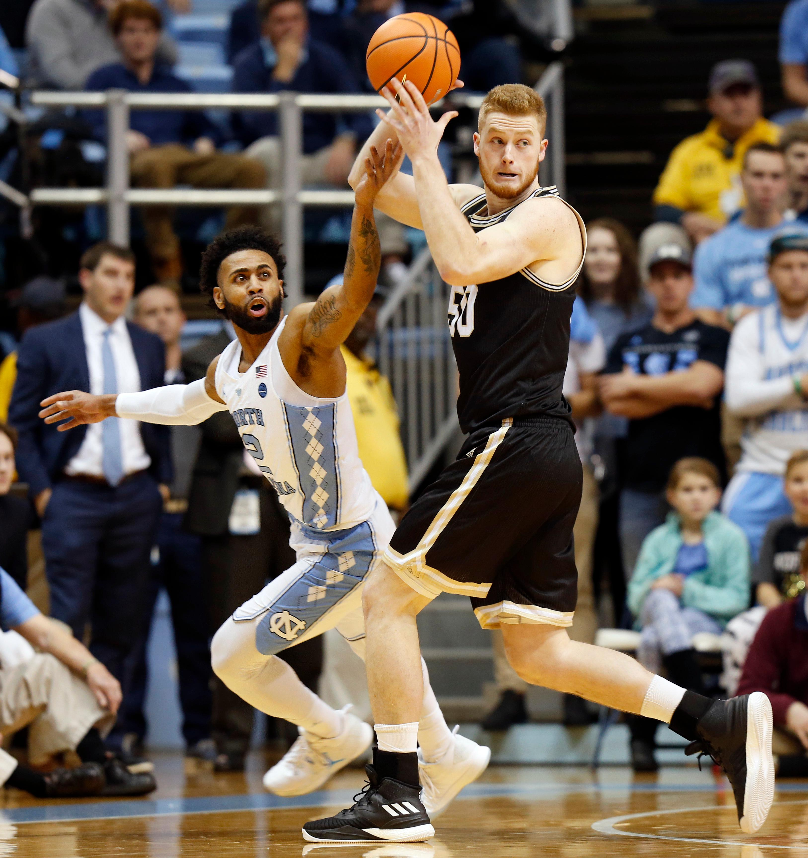 North Carolina Tar Heels guard Joel Berry II, left, battles Wofford Terriers center Matthew Pegram for the ball during the first half of an NCAA college basketball game in Chapel Hill, N.C., Wednesday, Dec. 20, 2017. (AP Photo/Ellen Ozier)