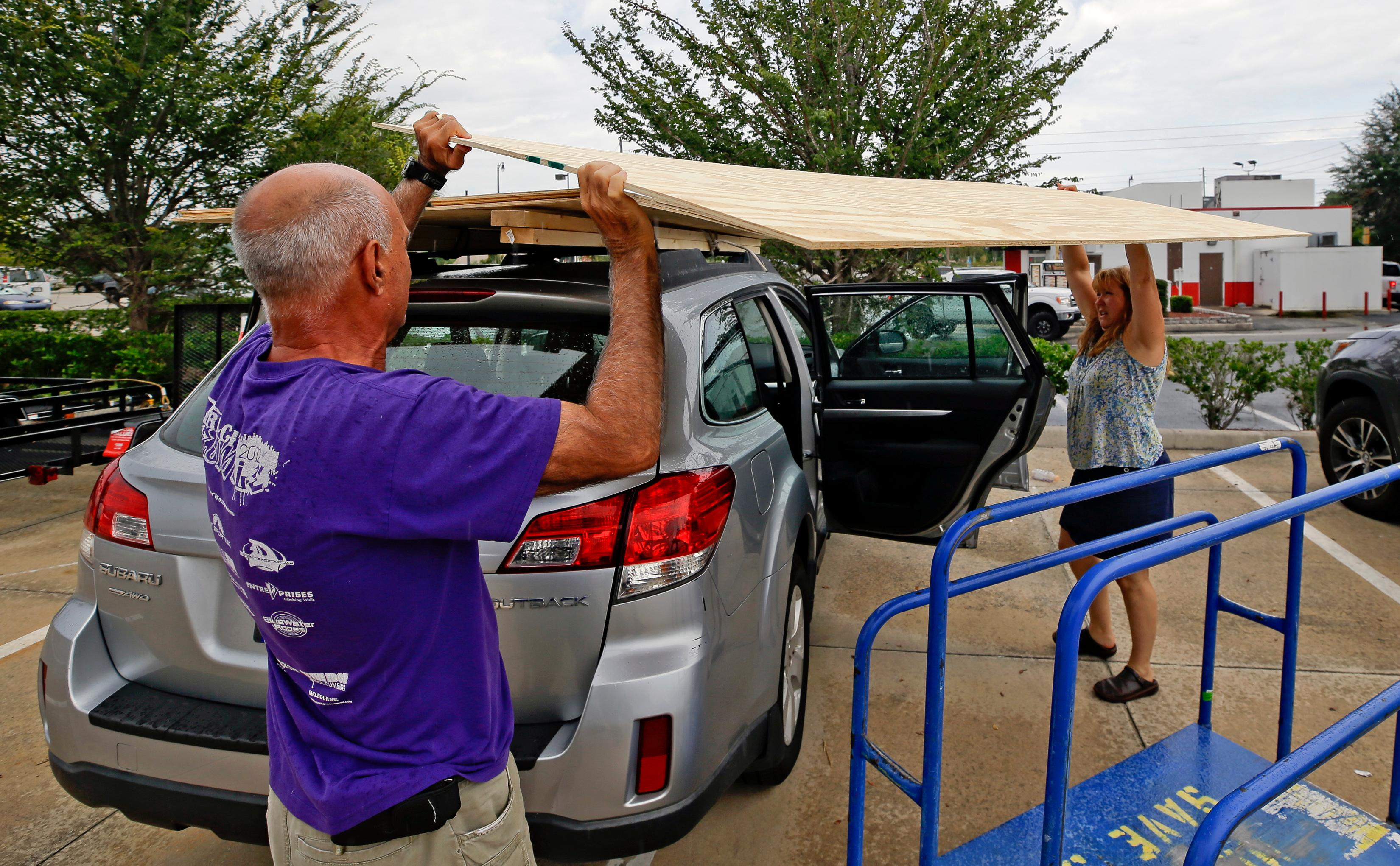 Alex, left, and Cynthia Stone, of Maitland, Fla. load plywood on the roof of their vehicle as they prepare for Hurricane Irma, Wednesday, Sept. 6, 2017, in Orlando, Fla.  Throughout Florida, officials and residents are making preparations, but forecasts indicate the Keys could take the country's first blow from the Category 5 storm.  (AP Photo/John Raoux)