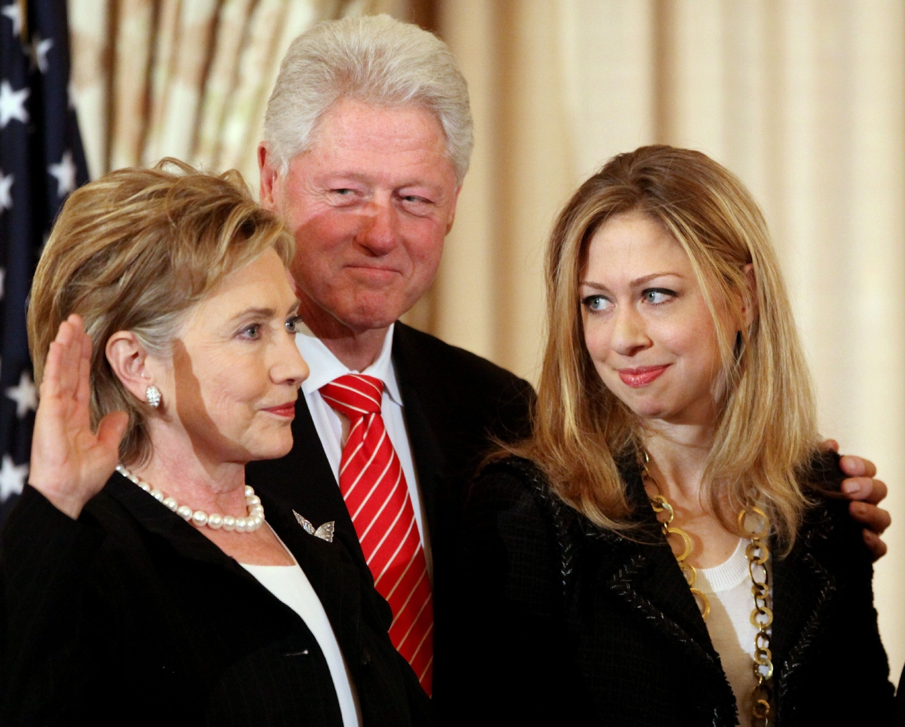 Former President Bill Clinton, center, and daughter Chelsea Clinton, right, look on during a ceremonial swearing-in for Secretary of State Hillary Rodham Clinton, Monday, Feb. 2, 2009, at the State Department in Washington. (AP Photo/Haraz N. Ghanbari)