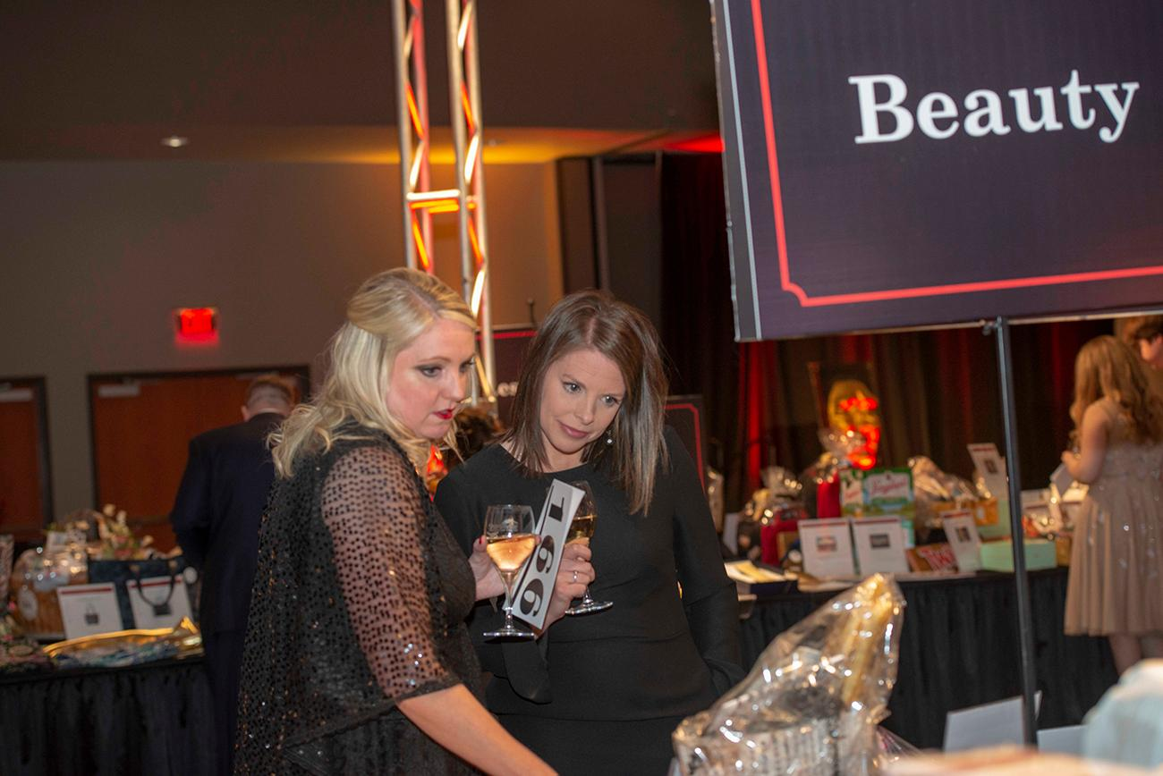 Michelle Kohler and Tara Grimes look at the items at the Silent Auction Table. / Image: Joe Simon // Published: 4.28.19