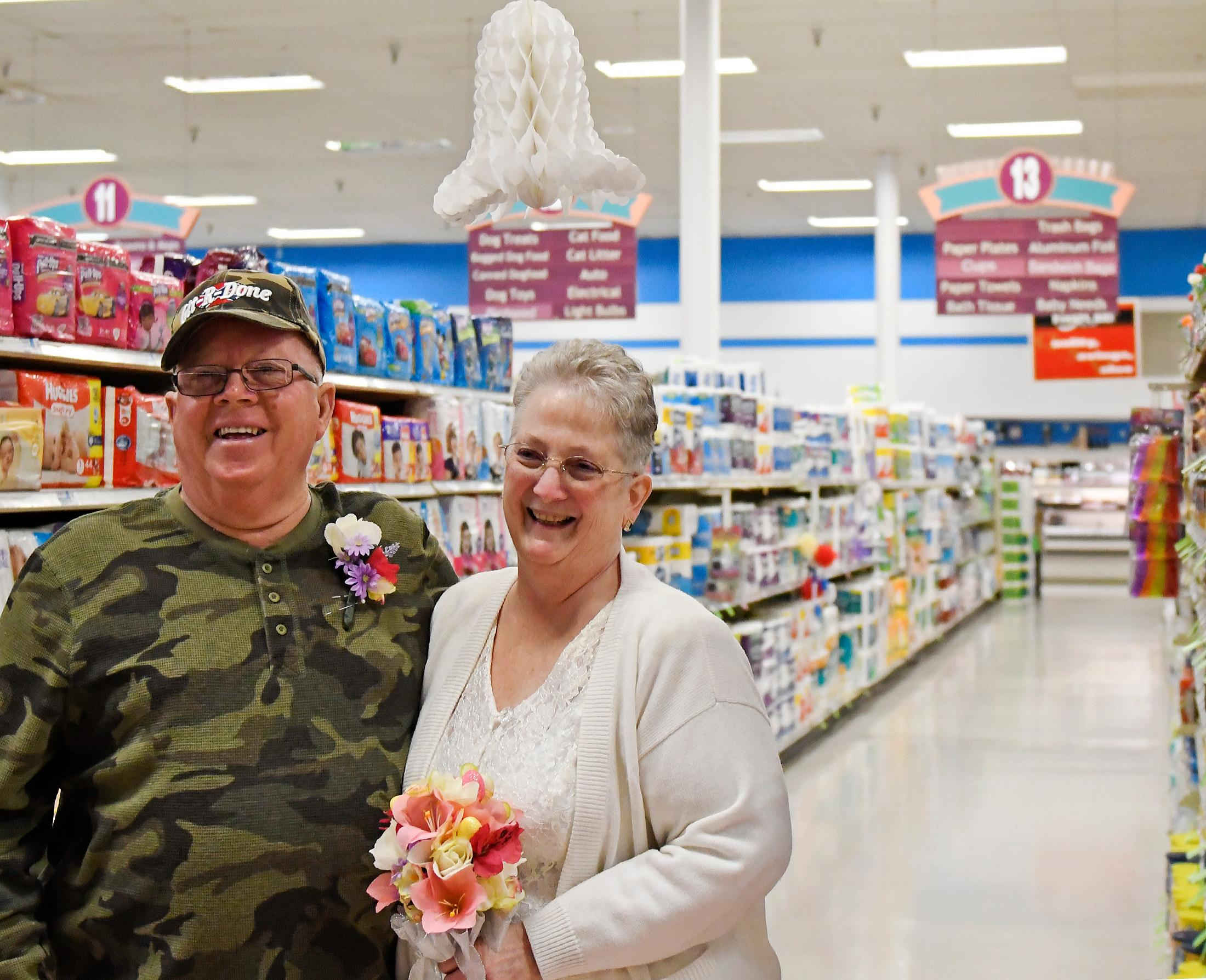 In this April 1, 2018 photo, Larry Spiering and Becky Smith pose for a photo where they held their wedding ceremony on Easter Sunday in aisle 13 of the Community Market in Lower Burrell, Pa. Smith said she was working at the supermarket when Spiering walked up and gave her a piece of paper with his name and phone number on it. She said it was only fitting that they married in the aisle where they met. (Jack Fordyce/Pittsburgh Tribune-Review via AP)