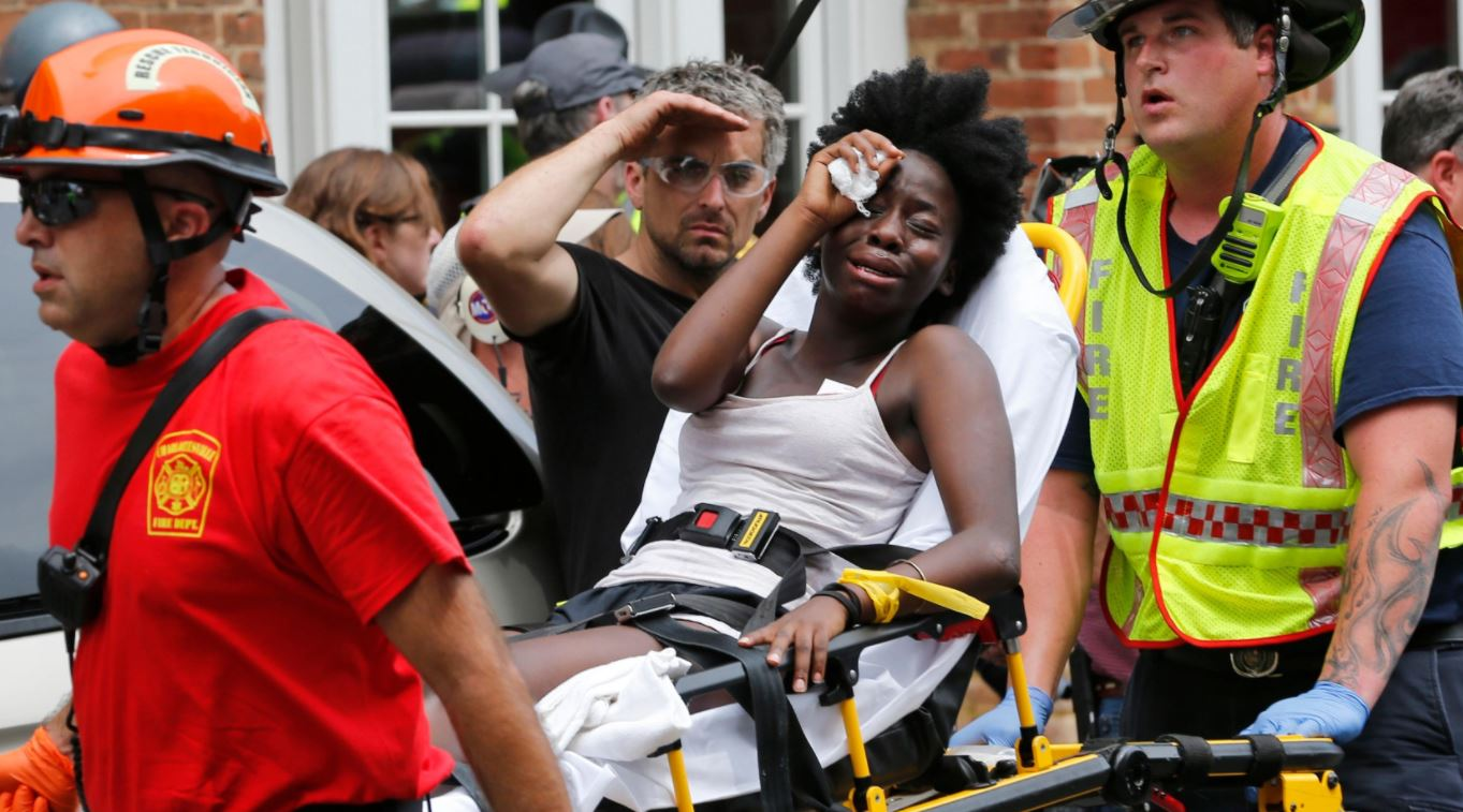 Rescue personnel help an injured woman after a car ran into a large group of protesters after an white nationalist rally in Charlottesville, Va.,