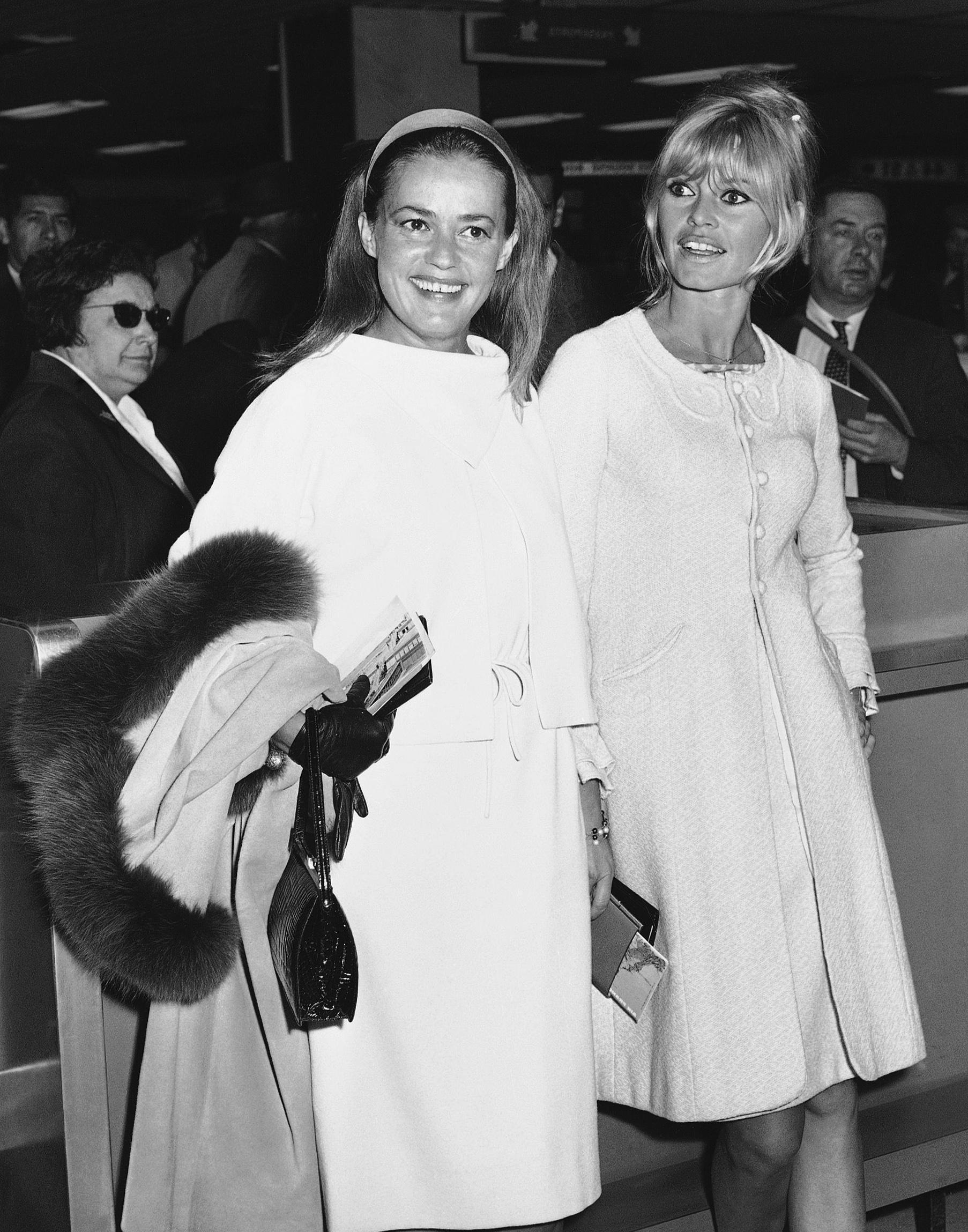 FILE - In this May 26, 1965 file photo Jeanne Moreau, left, and Brigitte Bardot are photographed as they arrive at Orly airport in Paris. French actress Jeanne Moreau, whose seven-decade career included work with Francois Truffaut, Orson Welles, Wim Wenders and other acclaimed directors, has died aged 89 it was announced Monday July 31, 2017. (AP Photo/File)