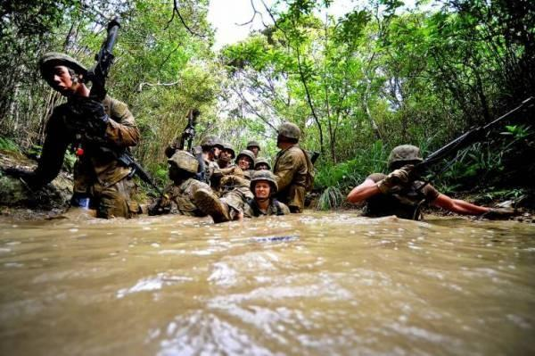 U.S. Navy Seabees carry a mock casualty on an improvised stretcher through shoulder-high muddy water while running 6-hour endurance course at Marine Corps Jungle Warfare Training Center in Okinawa, Japan. More than 60 Seabees attended the 8-day course.
