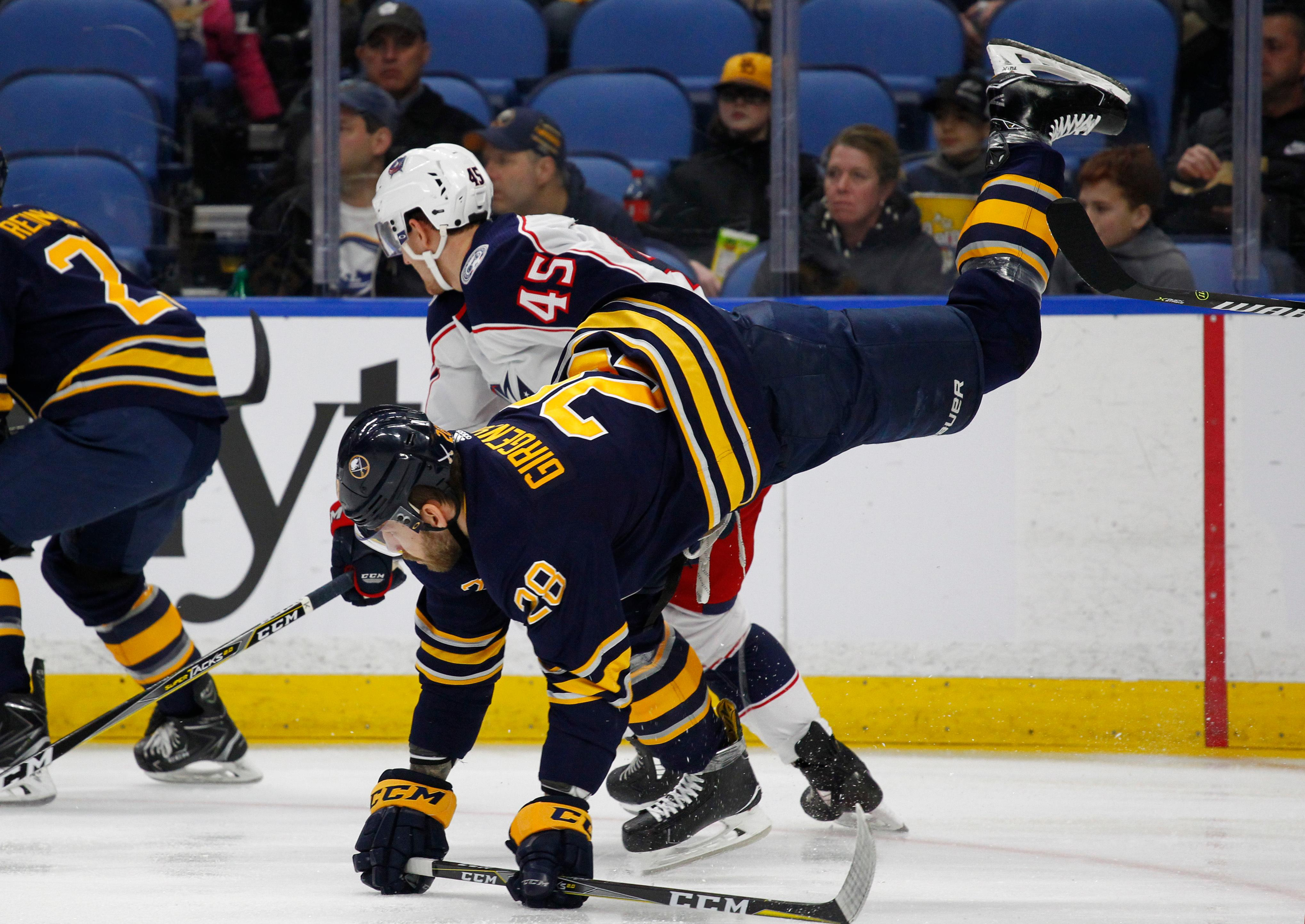 Buffalo Sabres forward Zemgus Girgensons (28) is tripped by Columbus Blue Jackets forward Lukas Sedlak (45) during the first period of an NHL hockey game Thursday, Jan. 11, 2018, in Buffalo, N.Y. (AP Photo/Jeffrey T. Barnes)
