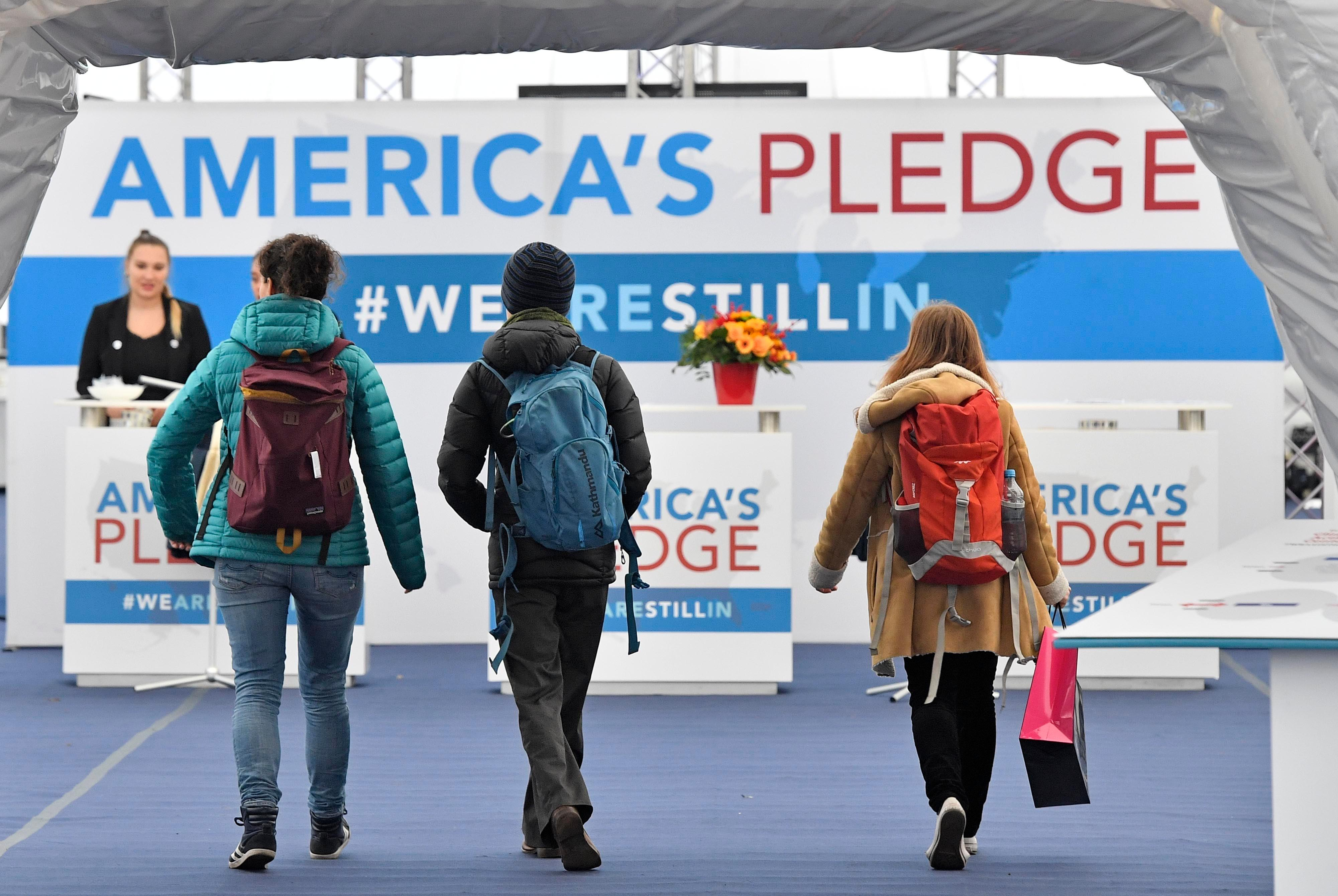 "Visitors enter the U.S. Climate Action Center at the COP 23 Fiji UN Climate Change Conference in Bonn, Germany, Thursday, Nov. 9, 2017. The non/government movement ""We are still in"" established the pavilion and forum where dozens of American leaders will convene throughout the negotiations. (AP Photo/Martin Meissner)"