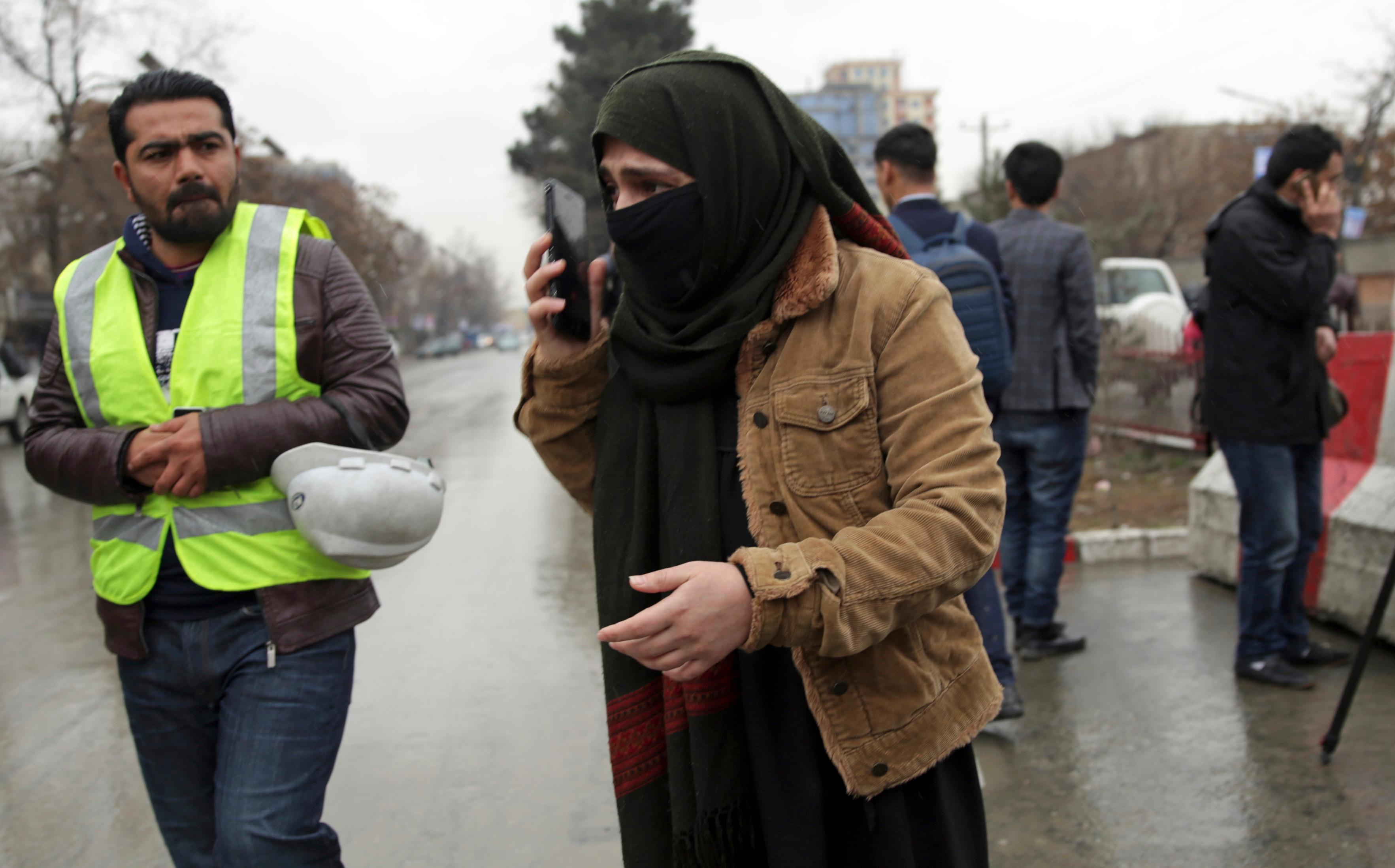 A woman talks to her phone as her relative were at site of a suicide bombing in the diplomatic area of capital Kabul, Afghanistan, Saturday, Feb. 24, 2018. Interior ministry spokesman Najib Danish said several people were wounded in Saturday's attack in the Shash Darak area of Kabul, near NATO headquarters and not far from the U.S. Embassy.(AP Photo/Massoud Hossaini)