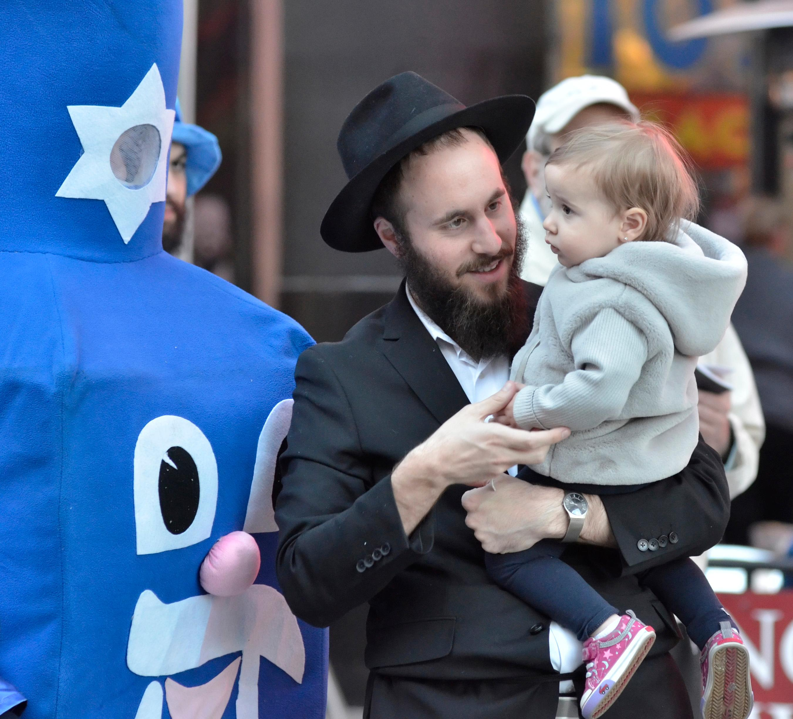 Rabbi Motti Harlig holds his son Rivkie, who is staring at one of the members of the Dancing Dreidels, during a menorah lighting ceremony. Rabbi Shea Harlig, of the Chabad Jewish Center of Southern Nevada, Las Vegas Mayor Carolyn Goodman, Jonathan Jossel, CEO of the Plaza hotel-casino, and Patrick Hughes, President and CEO of Fremont Street Experience, were on hand for the first night of Hanukkah which was marked with the lighting of a 20-foot Grand Menorah on Fremont Street in downtown Las Vegas on Tuesday, Dec. 12, 2017. CREDIT: Bill Hughes/Las Vegas News Bureau