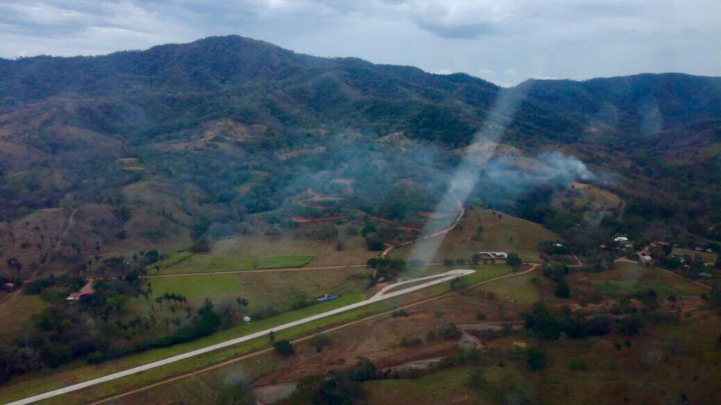 This photo released by Costa Rica's Public Safety Ministry shows smoke rising from the site of a plane crash near an air strip in Punta Islita, Guanacaste, Costa Rica, Sunday, Dec. 31, 2017. (Costa Rica's Public Safety Ministry via AP)