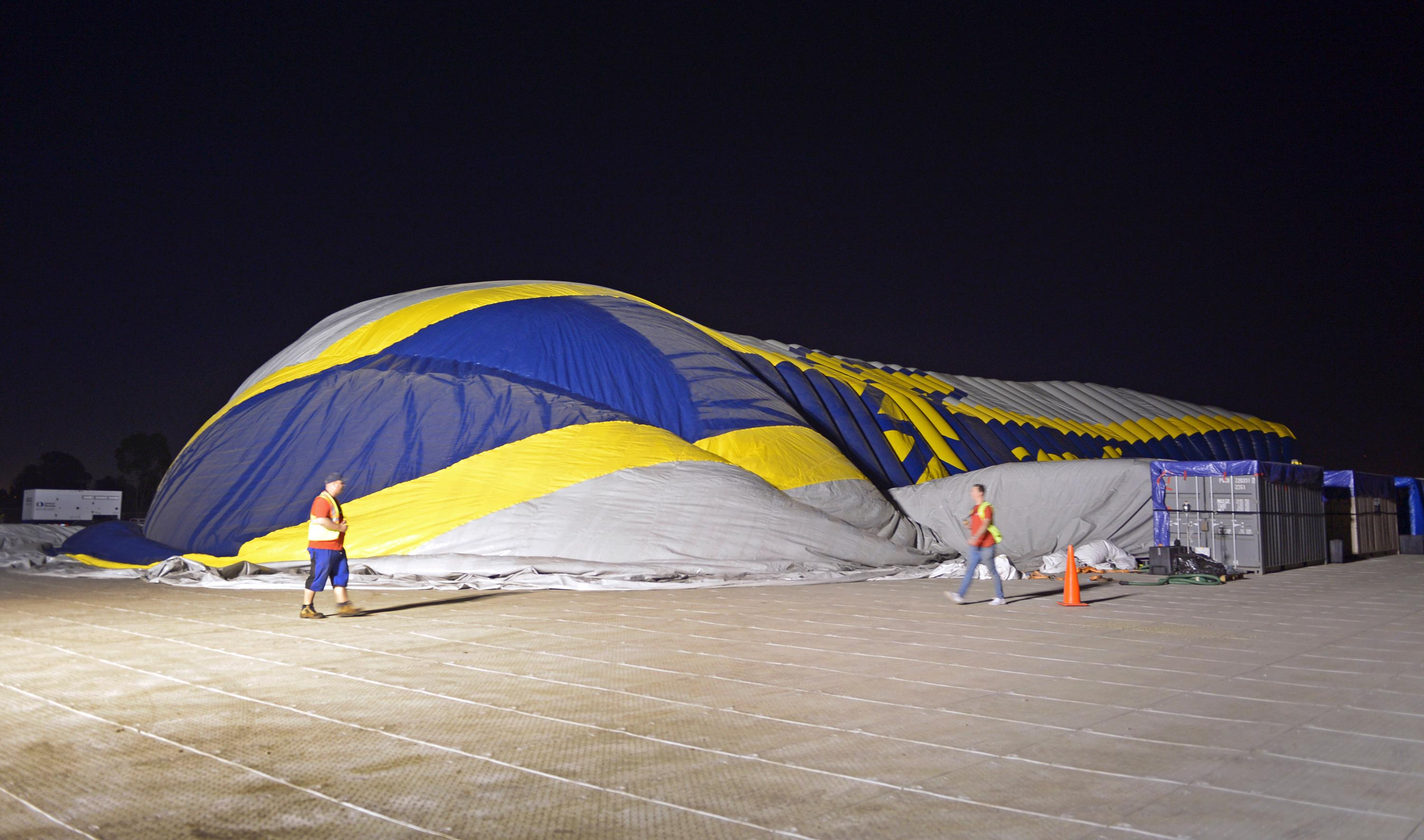 This photo provided by the Goodyear Tire & Rubber Co. shows a stage of the inflation of a giant inflatable hangar that will be the permanent home of one of the company's new semi-rigid airships, Wednesday, Dec. 13, 2017 in Carson, Calif. The building standing nine stories tall and stretching the length of a football field went up early Wednesday along Interstate 405 south of Los Angeles. (Goodyear Tire & Rubber Co. via AP)