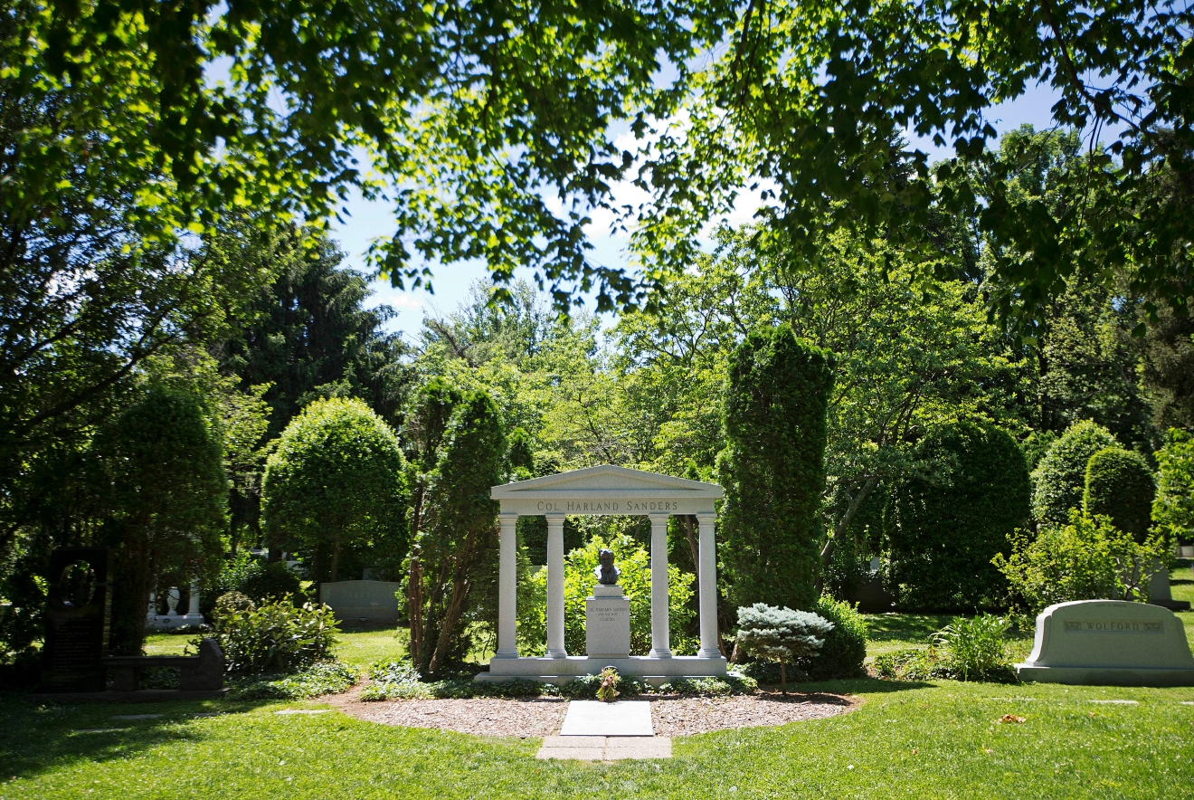 The granite memorial of Colonel Harlan Sanders, the founder of Kentucky Fried Chicken, stands at Cave Hill Cemetery Tuesday, June 7, 2016, in Louisville, Ky. Muhammad Ali's burial will be in Cave Hill Cemetery, the final resting place for many of the city's most prominent residents. The luminaries include Sanders whose granite memorial features a bust of the goateed entrepreneur. Ali's gravesite will far more subdued, in contrast to his oversized personality and life. A modest marker, in accord with Muslim tradition, is planned, said his attorney, Ron Tweel. (AP Photo/David Goldman)