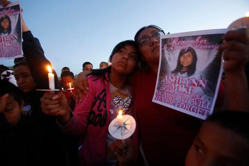 This Tuesday, May 4, 2016 photo Klandre Willie, left, and her mother, Jaycelyn Blackie, participate in a candlelight vigil, for Ashlynne Mike at the San Juan Chapter House in Lower Fruitland, N.M.  The FBI said Mike, was abducted after school on Monday and her body was found the next day.  Tom Begaye was arrested in connection with Mike's disappearance and death.  (Jon Austria/The Daily Times via AP) MANDATORY CREDIT