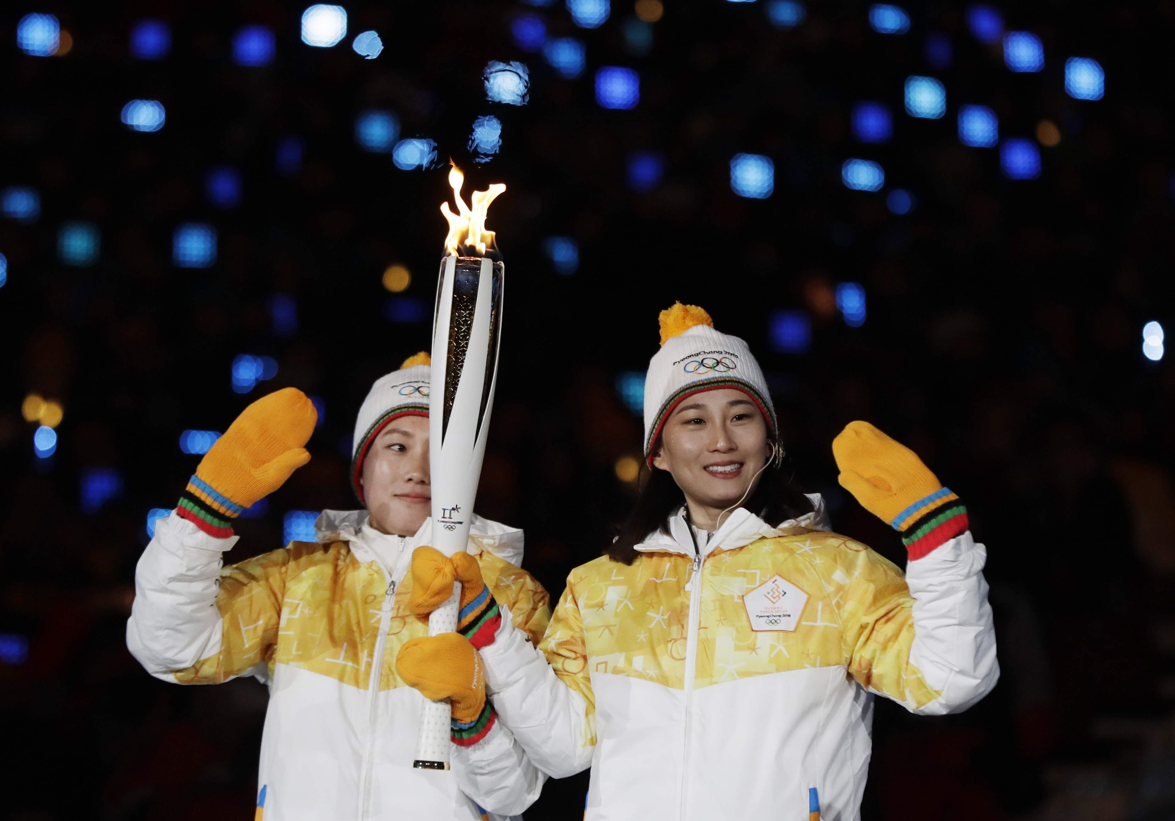 North Korea's Jong Su Hyon, left, and South Korea's Park Jong-ah carry the torch in the stadium during the opening ceremony of the 2018 Winter Olympics in Pyeongchang, South Korea, Friday, Feb. 9, 2018. (AP Photo/Petr David Josek)