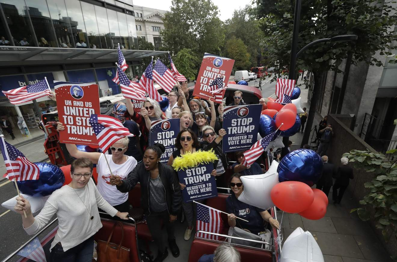 Opponents of U.S. Republican presidential candidate Donald Trump travel aboard an open-top double decker þÄúSTOP TRUMPþÄù bus, encouraging expats to register to vote for the upcoming United States presidential election, as they tour central London, Wednesday, Sept. 21, 2016. The bus event was organised by the global online campaign movement Avaaz as the deadline to register to vote is approaching in some American states. (AP Photo/Matt Dunham)