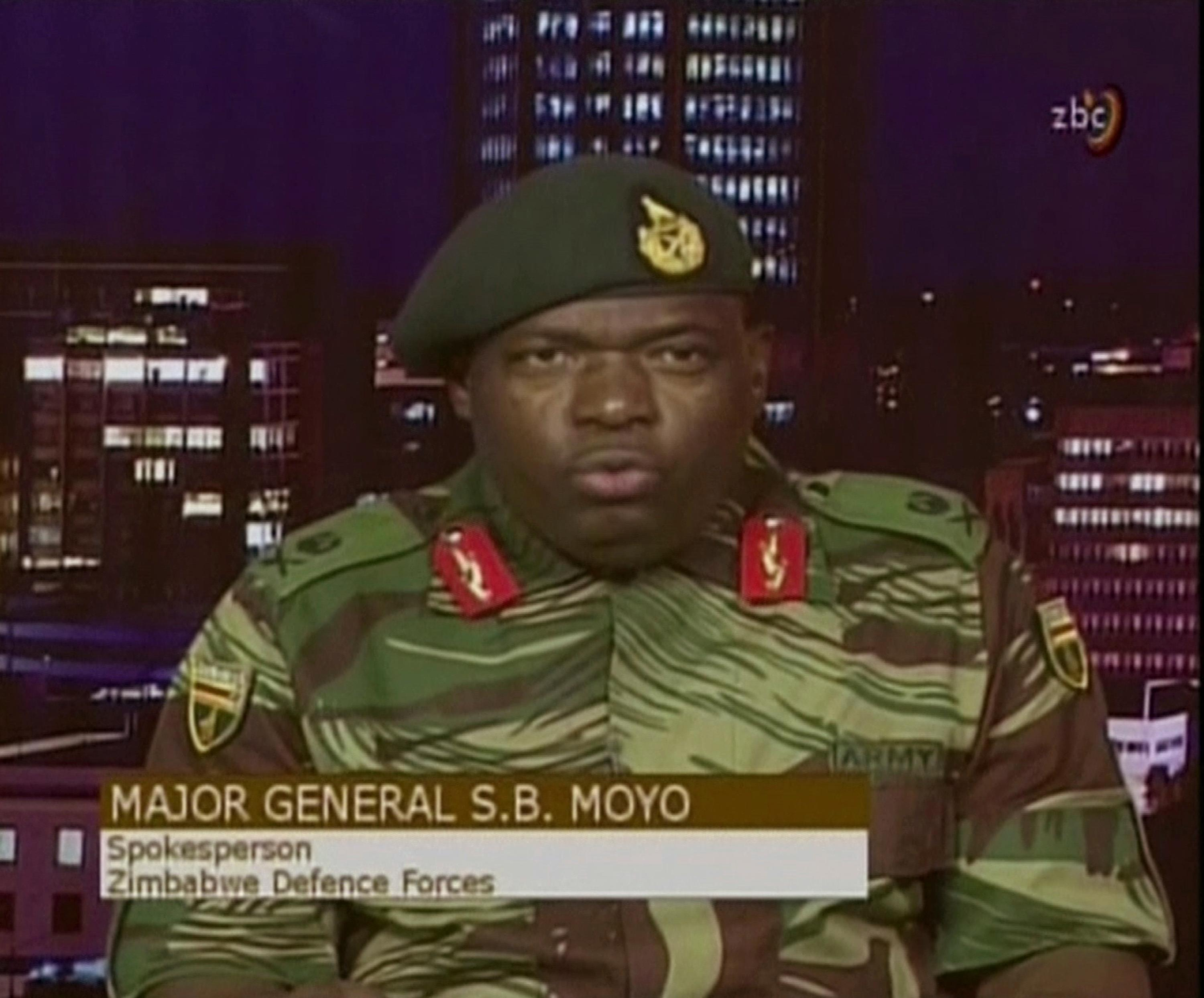 "In this image made from video, Major Gen. S.B. Moyo, Spokesperson for the Zimbabwe Defense Forces addresses to the nation in Harare, Zimbabwe Wednesday, Nov. 15, 2017. The army spokesman said early Wednesday the military is targeting ""criminals"" around President Robert Mugabe, and sought to reassure the country that order will be restored. (ZBC via AP)"
