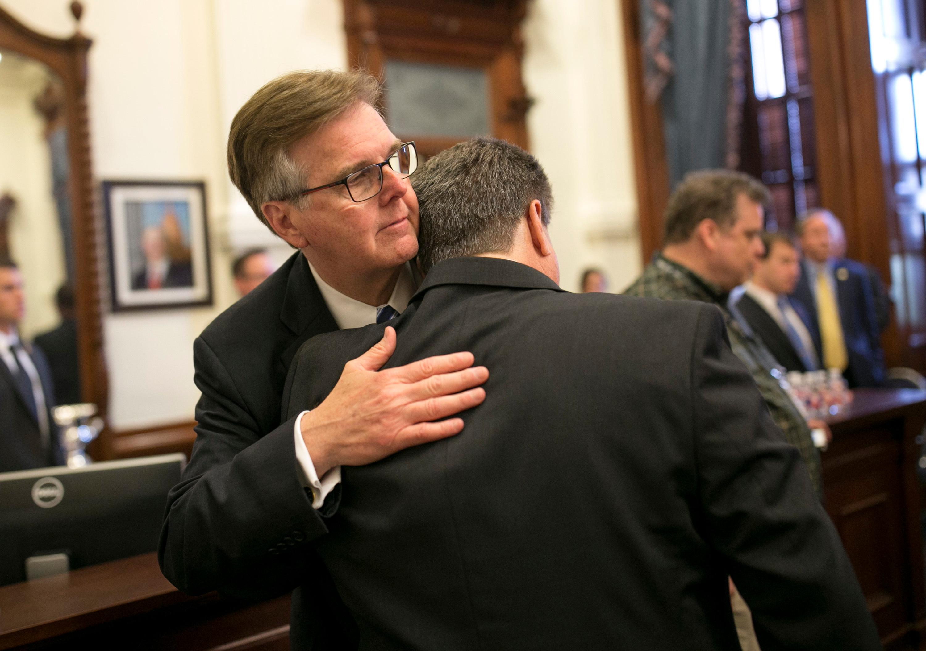 Lt. Gov. Dan Patrick, left, hugs Scot Rice during a discussion about guns in schools at the Governor's Reception Room at the Capitol in Austin, Texas, Thursday, May 24, 2018. Rice's wife Flo Rice, a substitute teacher, was carried from the Santa Fe scene of last week's school shooting after she was shot in the leg. (Jay Janner/Austin American-Statesman via AP)