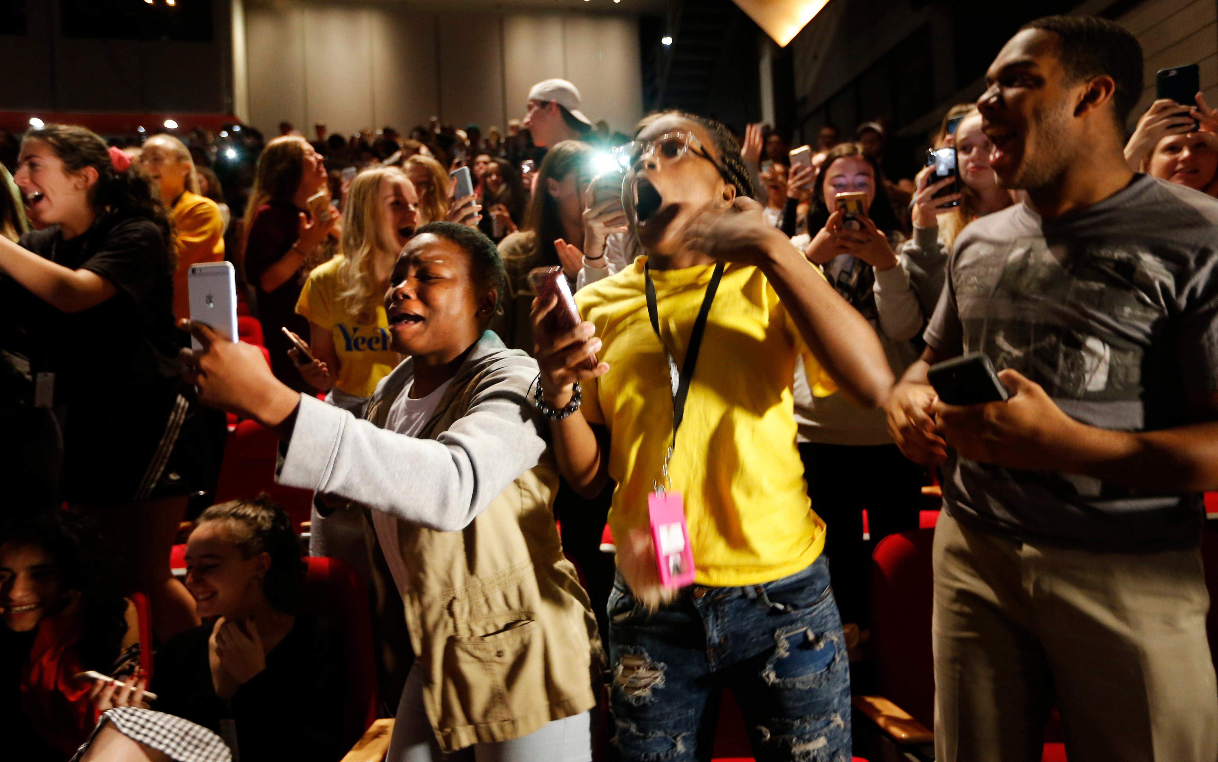 In this Sept. 12, 2018 photo, Kir'Ondria Woods, Jamilla Johnson and Lance Jackson yell as comedian and actor Kevin Hart takes the stage as the principal for a day at Booker T. Washington High School in Dallas. Hart was named principal for the day. Hart was in town promoting his new movie, Night School. (Vernon Bryant/The Dallas Morning News via AP)