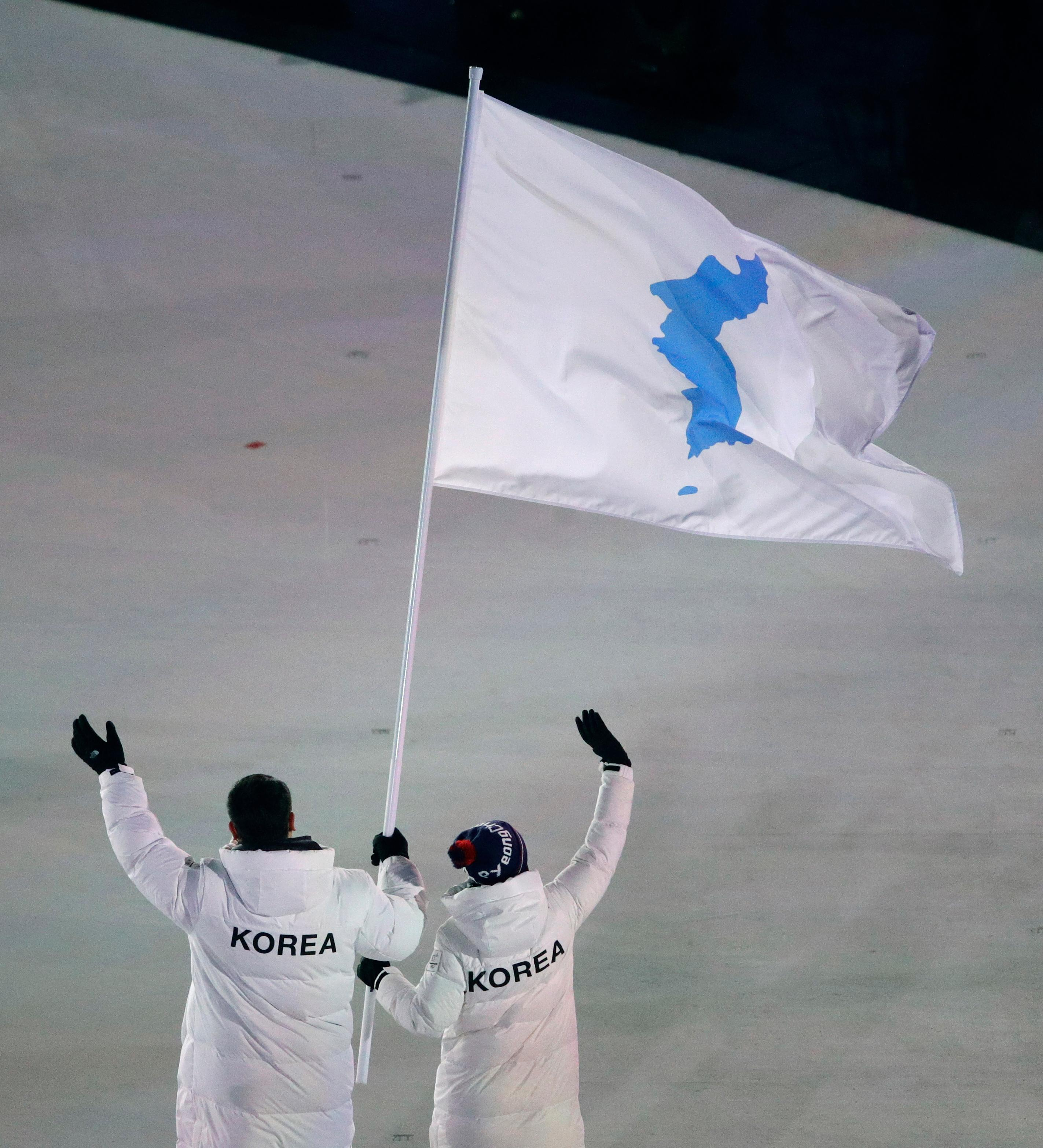 North Korea's Hwang Chung Gum and South Korea's Won Yun-jong arrive during the opening ceremony of the 2018 Winter Olympics in Pyeongchang, South Korea, Friday, Feb. 9, 2018. (AP Photo/Charlie Riedel)