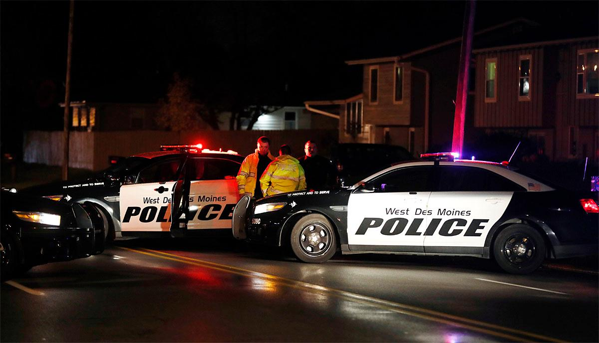 Law enforcement officials investigate at the scene of a shooting, Wednesday, Nov. 2, 2016, in Urbandale, Iowa. Two Des Moines area police officers were shot to death early Wednesday in ambush-style attacks while they were sitting in their patrol cars, and police are searching for suspects, authorities said. (AP Photo/Charlie Neibergall)