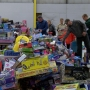 Volunteers help sort toys for kids in need