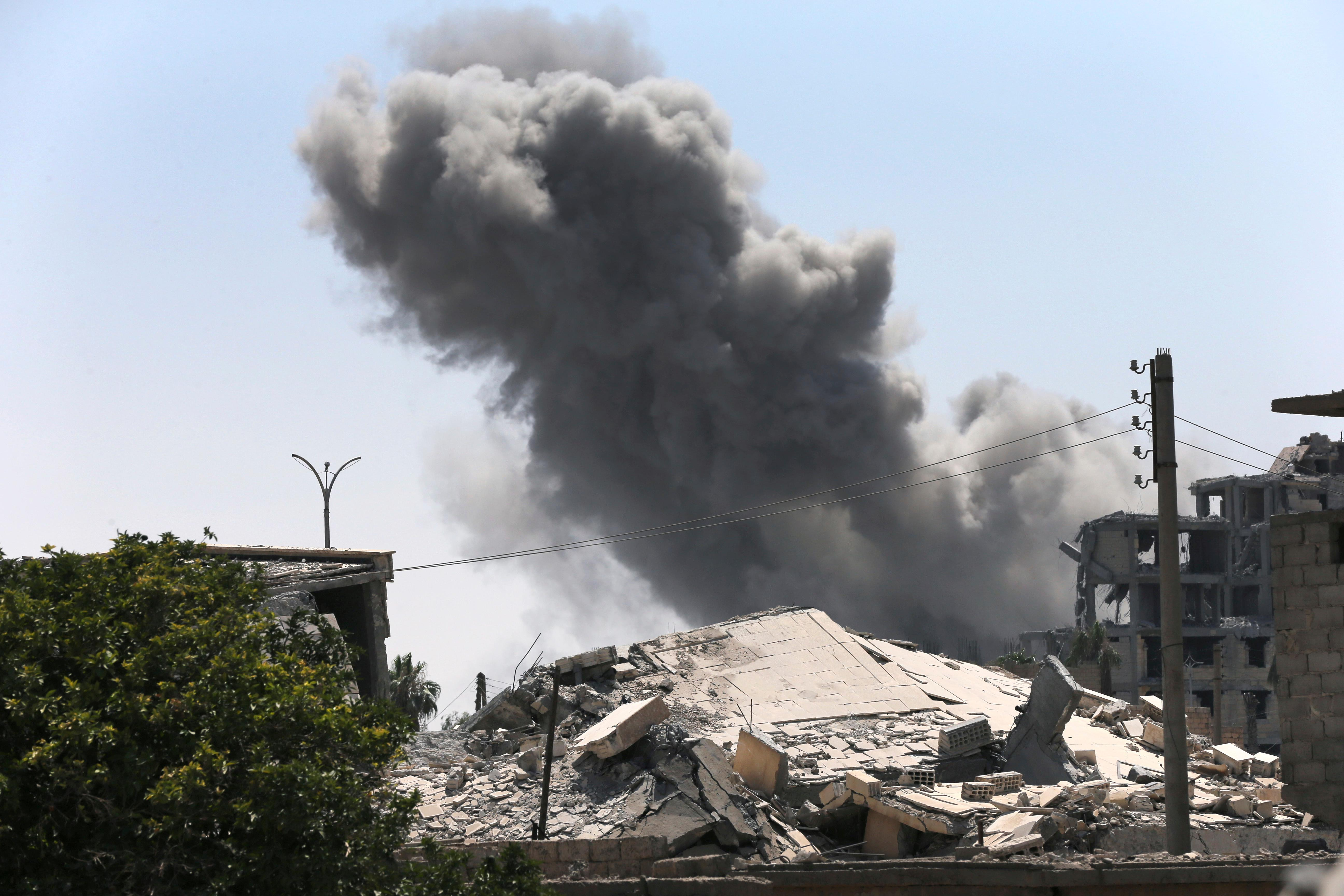 Black smoke rises from a coalition airstrike which attacked an Islamic State militant position, on the front line on the eastern side of Raqqa, Syria, Wednesday, July 26, 2017. Kurdish forces have gained confidence in light of open U.S. support to their forces, particularly as the battle for Raqqa took off. Despite Turkish protests, the U.S. sent new weapons and vehicles to the YPG to enable it in the fight against IS. (AP Photo/Hussein Malla)