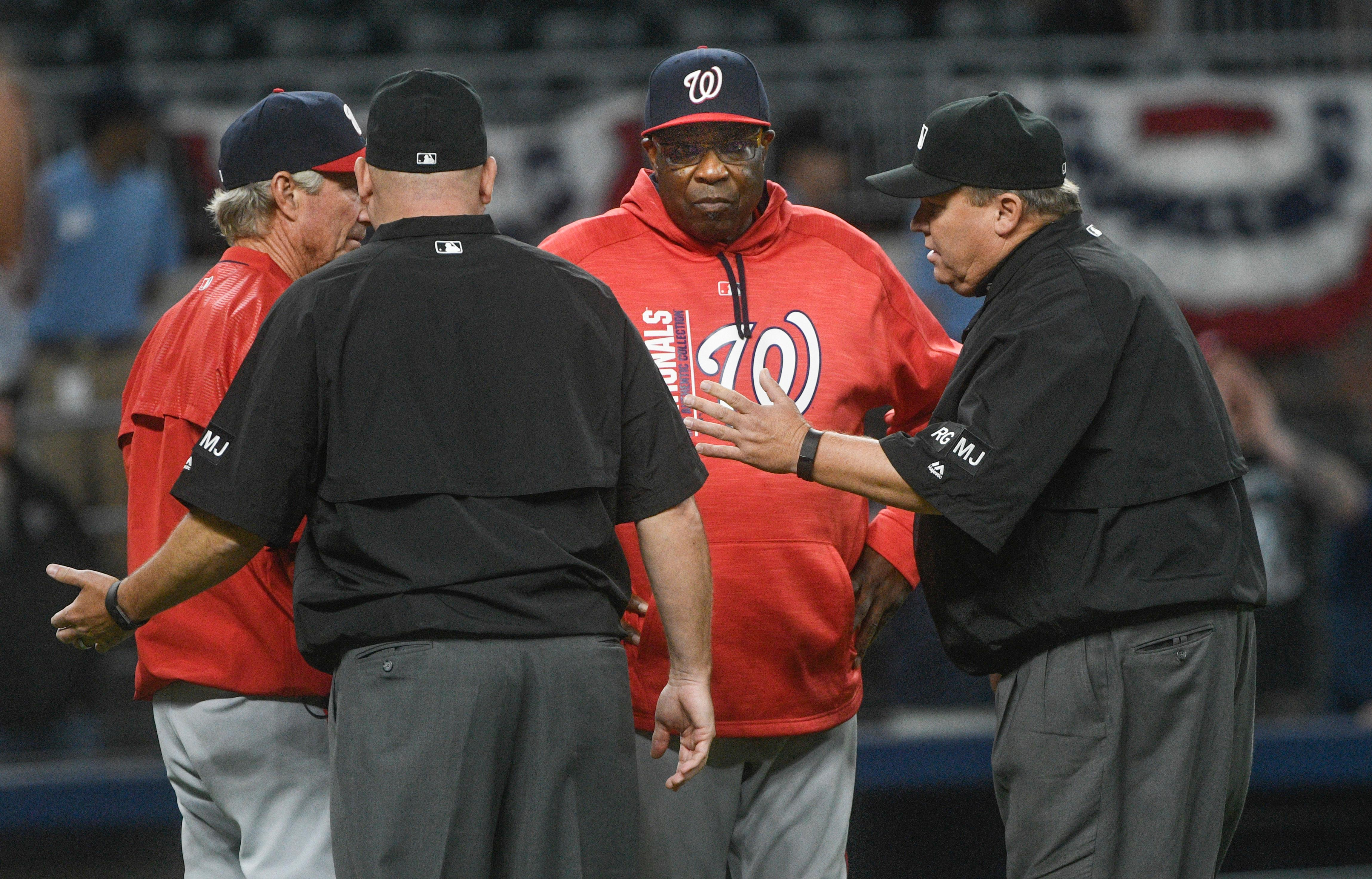 Umpires tell Washington Nationals manager Dusty Baker, second from right, and bench coach Chris Speier, left, the game was not over after the two and players came onto the field to celebrate during the ninth inning of a baseball game against the Atlanta Braves, Tuesday, April 18, 2017, in Atlanta. Washington won 3-1. (AP Photo/John Amis)