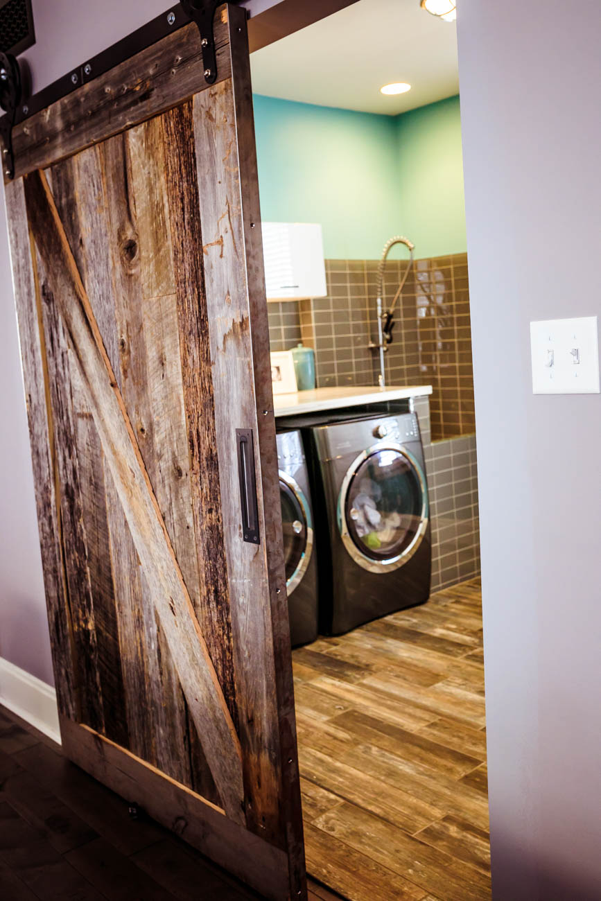 The first floor laundry room of the Dunki-Jacobs home in Oakley. The barn wood sliding door was made by Rustic Refinery in Oakley. / Image: Amy Elisabeth Spasoff // Published: 3.13.18