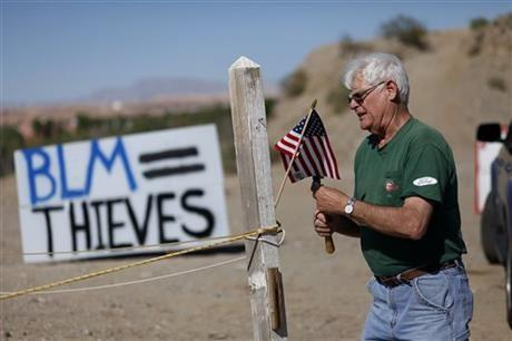 "Jim Olson puts up a flag near what was the Bureau of Land Management's ""first amendment area"" in Bunkerville, Nev. Thursday, April 10, 2014."