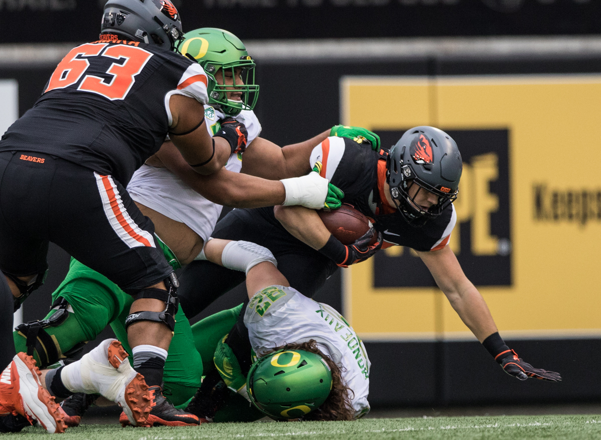 Oregon State Beavers running back Ryan Nall (#34) is tackled by Oregon Ducks defenders Henry Mondeaux (#92) and Wayne Tei-Kirby (#71). The Oregon State University Beavers hosted the 120th Civil War against the University of Oregon Ducks on Saturday afternoon at Reser Stadium in Corvallis, Ore. The Oregon State Beavers beat the Oregon Ducks 34-24 breaking an eight-year losing streak. Photo by Austin Hicks, Oregon News Lab