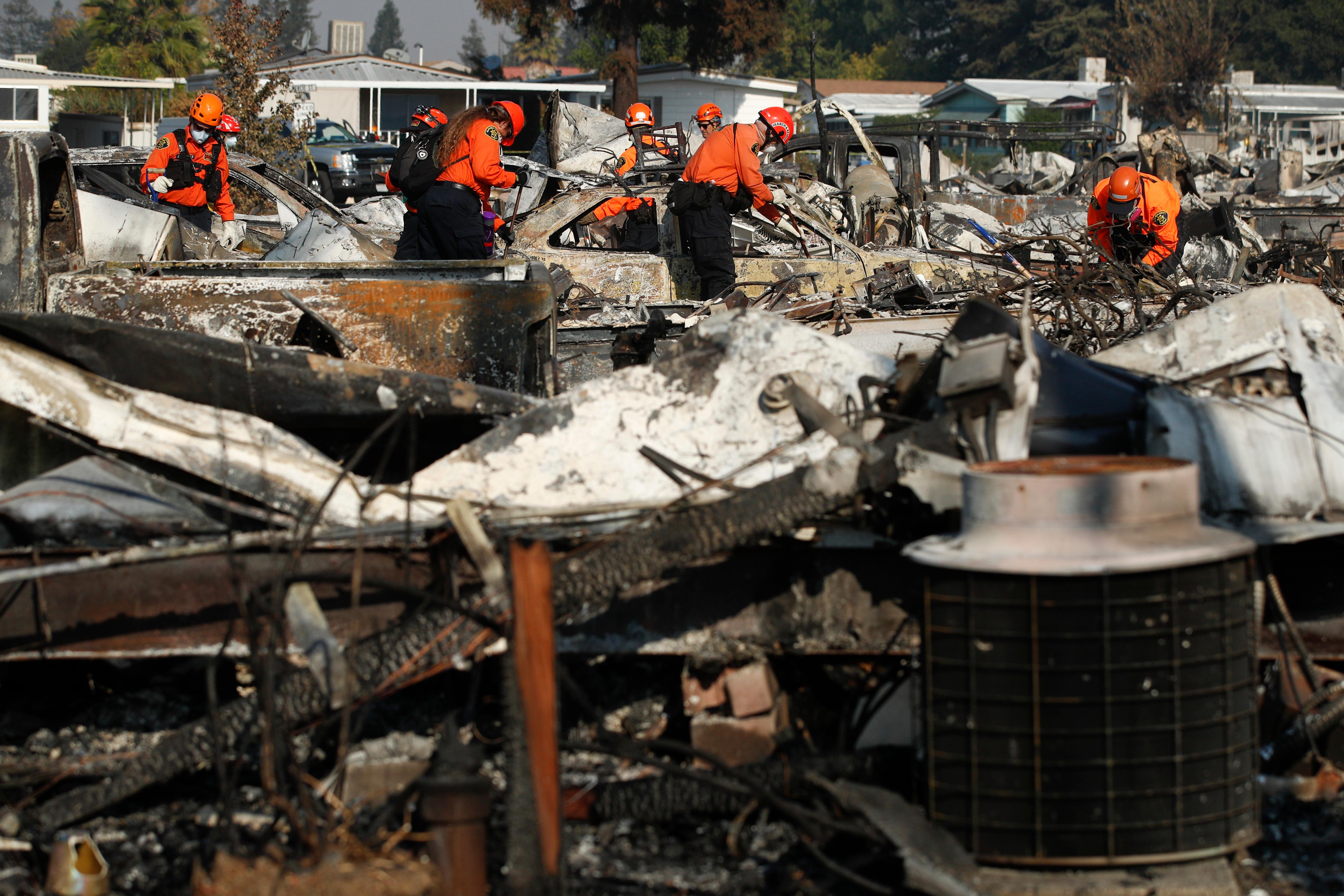 Members of a search and rescue team search through the rubble of mobile homes destroyed by a wildfire Monday, Oct. 16, 2017, in Santa Rosa, Calif. With the winds dying down, fire crews gained ground as they battled wildfires that have devastated California wine country and other parts of the state over the past week, and thousands of people got the all-clear to return home. (AP Photo/Jae C. Hong)