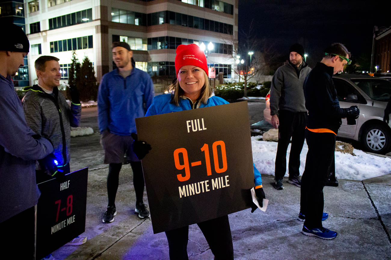 Erin Lawry holds one of the signs for runners to establish which group they want to stay with on the route, based on their pace. / Image: Katie Robinson, Cincinnati Refined // Published: 1.27.19{ }