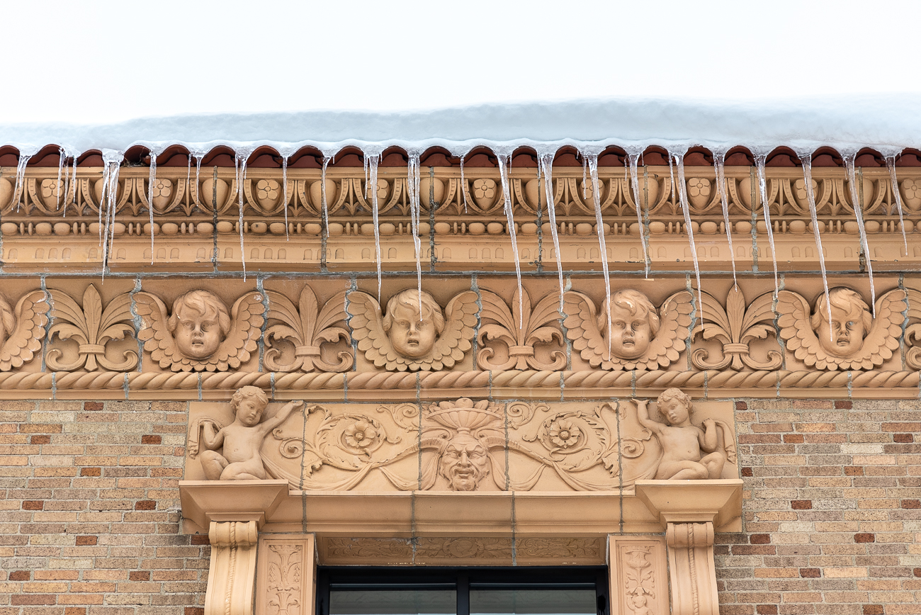 The exterior of the Madcap Educational Center is covered in intricate architectural detail from its original design. Faces of cherubs, floral patters, grotesques, and bells (for Cincinnati Bell) are visible. / Image: Phil Armstrong, Cincinnati Refined // Published: 1.26.19