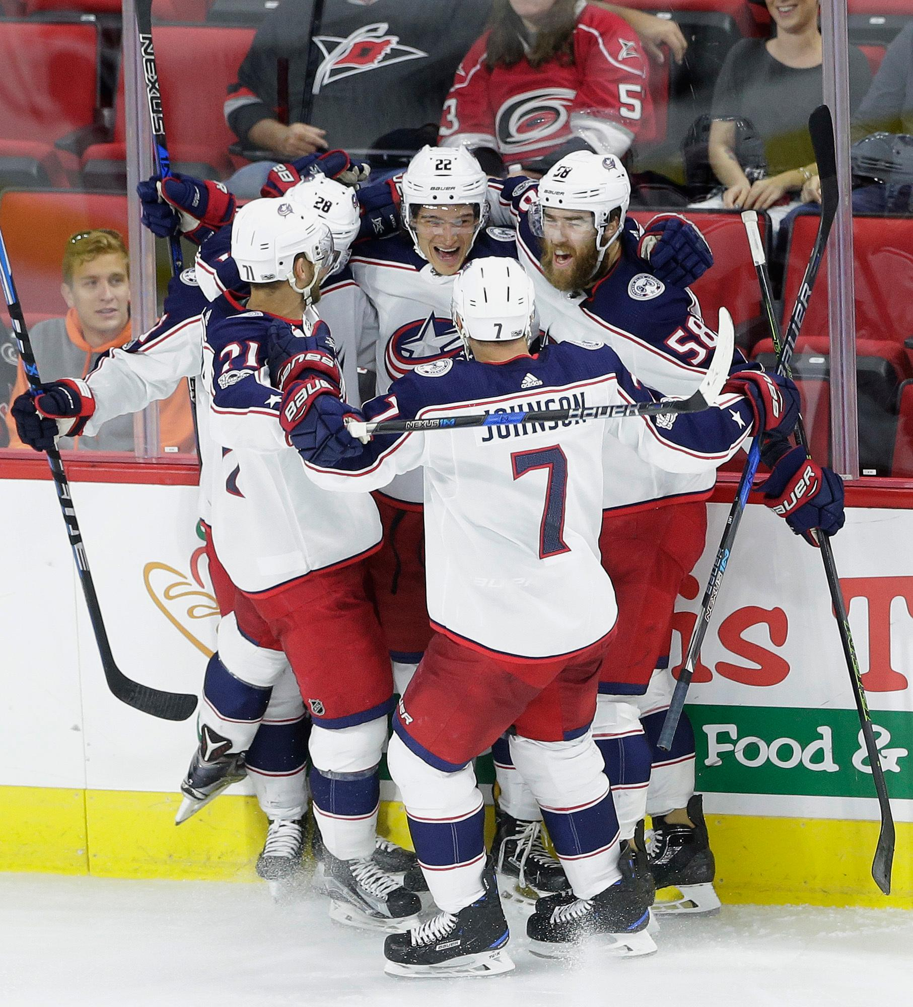 Columbus Blue Jackets' Sonny Milano (22) is congratulated by Jack Johnson (7), David Savard (58), Oliver Bjorkstrand (28), of Denmark, and Nick Foligno (71) following Milano's goal against the Carolina Hurricanes during the third period of an NHL hockey game in Raleigh, N.C., Tuesday, Oct. 10, 2017. Columbus won 2-1 in overtime. (AP Photo/Gerry Broome)