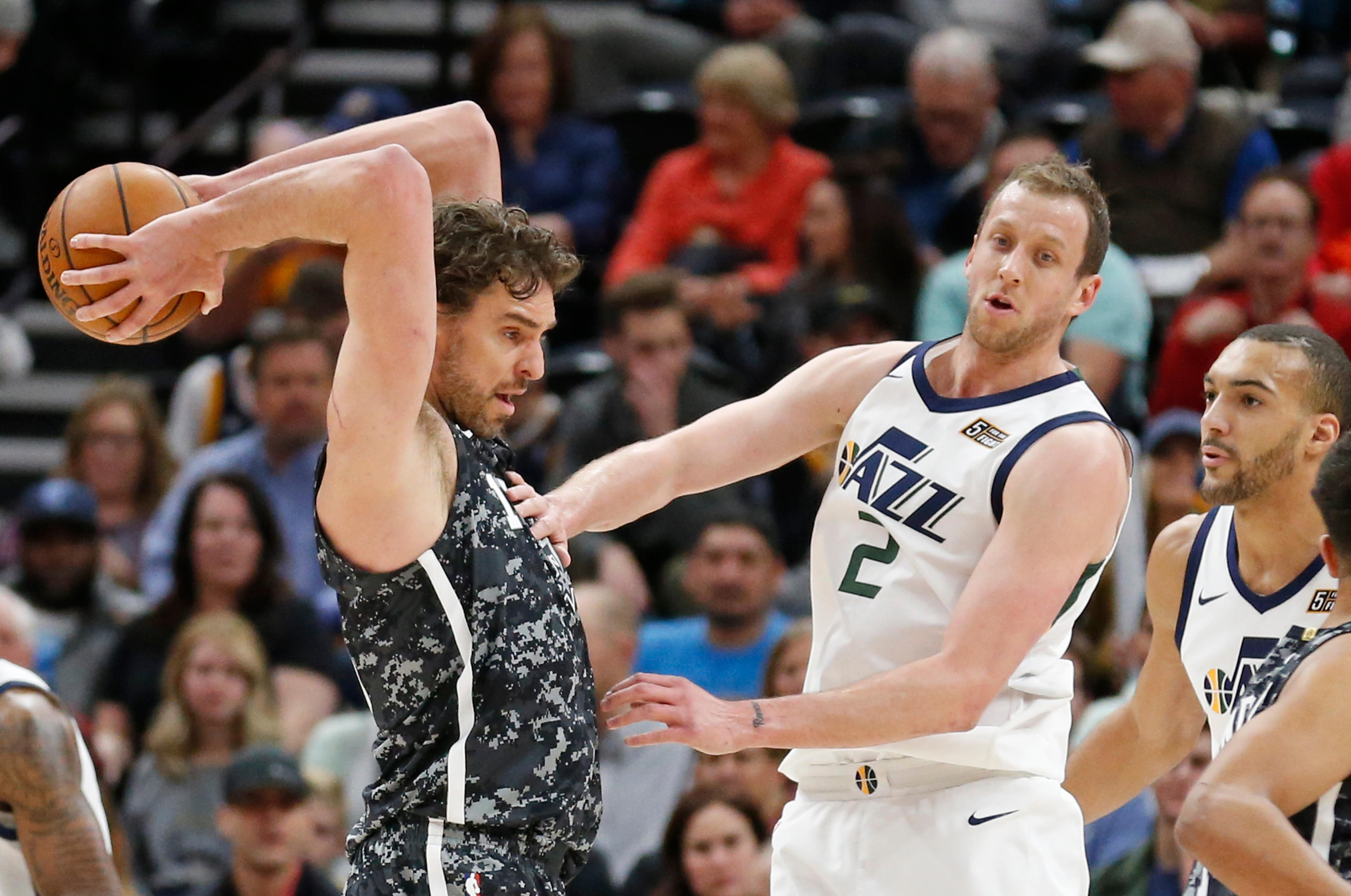San Antonio Spurs center Pau Gasol, left, passes the ball as Utah Jazz's Joe Ingles (2) and Rudy Gobert, right, look on in the first half during an NBA basketball game Monday, Feb. 12, 2018, in Salt Lake City. (AP Photo/Rick Bowmer)