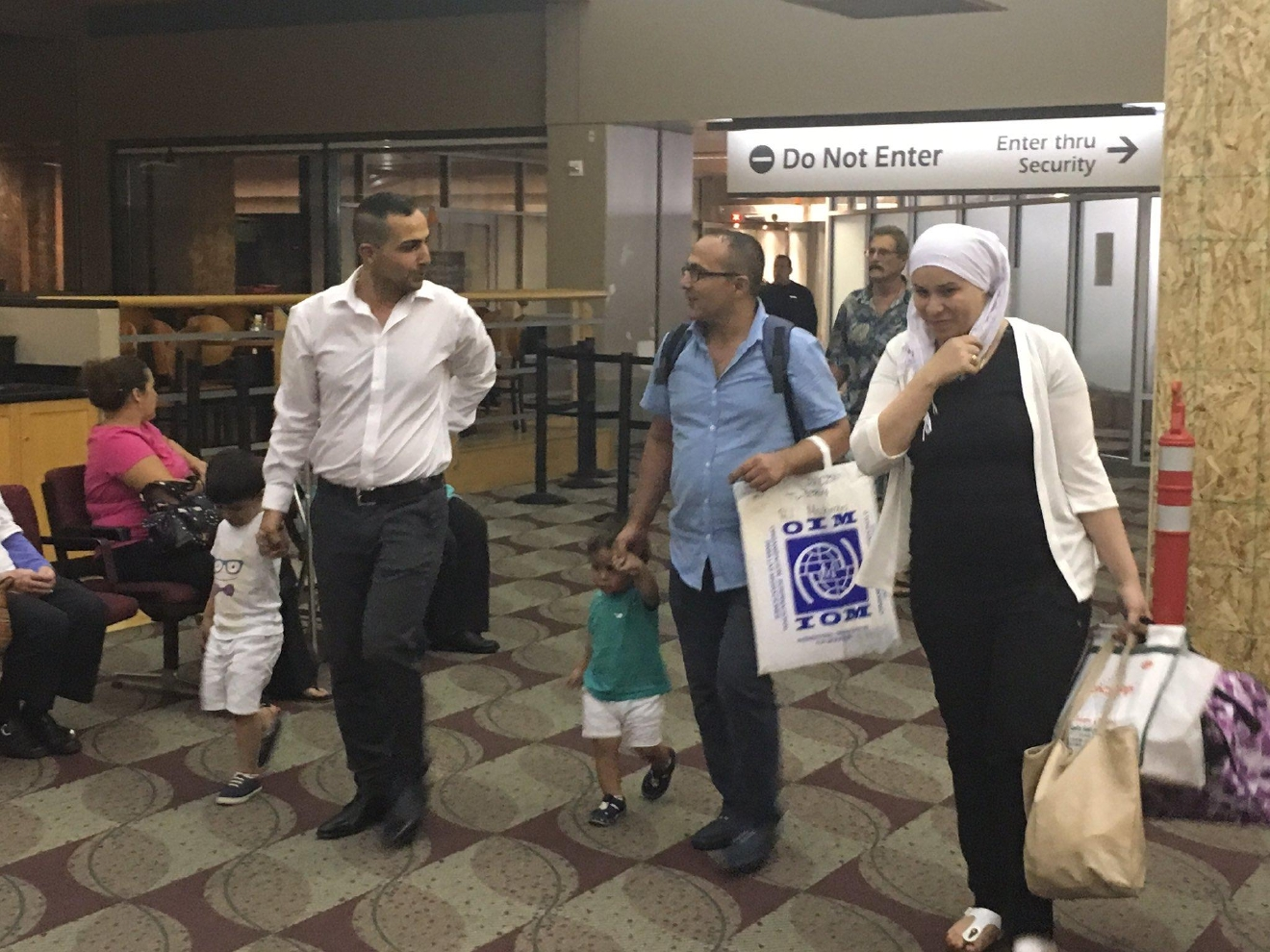 An eager crowd welcomed the Syrian refugee family to Eugene Wednesday night. About 100 volunteers worked to help the family relocate and many of them were at the airport holding posters. (SBG photo)