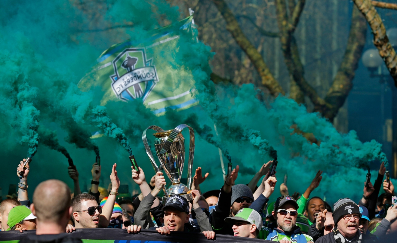Members of the Emerald City Supporters hold up smoke effects as they take part in the traditional March to the Match with the 2016 MLS Cup trophy before an MLS soccer match between the Seattle Sounders and the New York Red Bulls, Sunday, March 19, 2017, in Seattle. (AP Photo/Ted S. Warren)