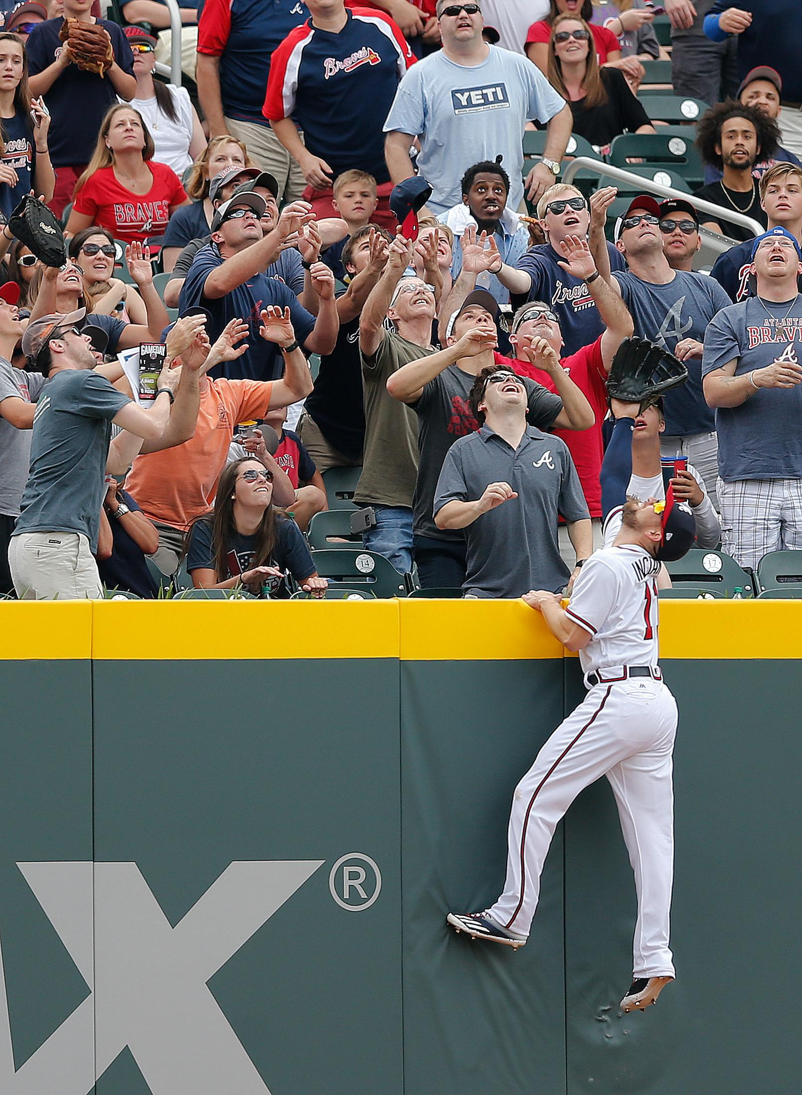 Atlanta Braves center fielder Ender Inciarte (11) goes up the wall as fans reach for a ball ht for a home run by San Diego Padres' Ryan Schimpf in the second inning of a baseball game Sunday, April 16, 2017, in Atlanta. (AP Photo/John Bazemore)