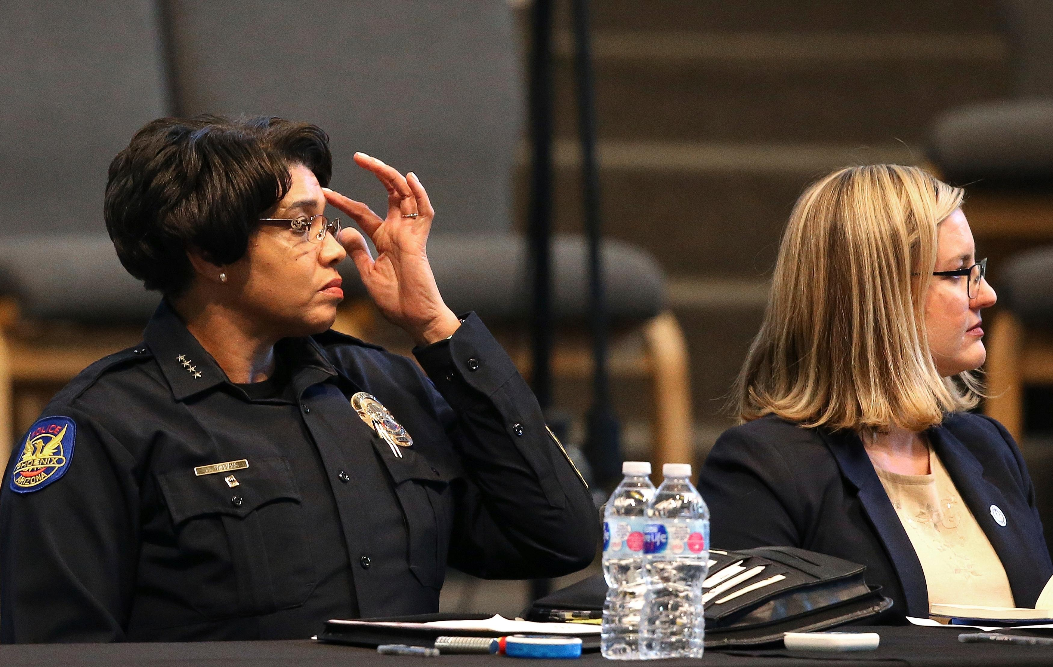 Phoenix Police Chief Jeri Williams, left, and Mayor Kate Gallego, right, listen to a speaker at a community meeting, Tuesday, June 18, 2019, in Phoenix.{ } (AP Photo/Ross D. Franklin)