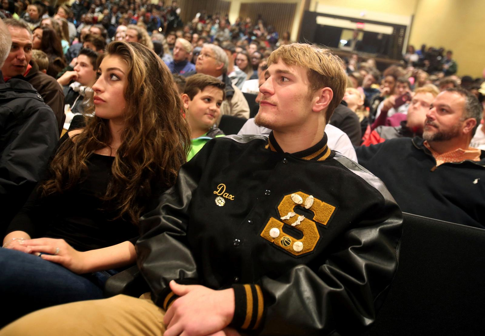 Shelby High School football player Dax Hollifield sits in a full auditorium as he                    waits to reveal his college decision during a signing day event at Shelby High School in Shelby, N.C. Wednesday, Feb. 7, 2018. Hollifield chose to attend Virginia Tech. (Brittany Randolph/The Star via AP)