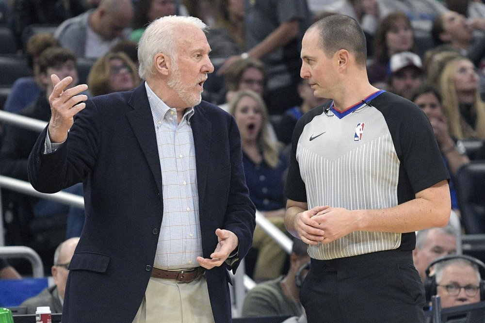 San Antonio Spurs head coach Gregg Popovich, left, talks with official Marat Kogut during the first half of an NBA basketball game against the Orlando Magic, Friday, Nov. 15, 2019, in Orlando, Fla. (AP Photo/Phelan M. Ebenhack)