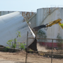 Workers demolish giant oil tanks from one of the area's last remaining waterfront oil farm