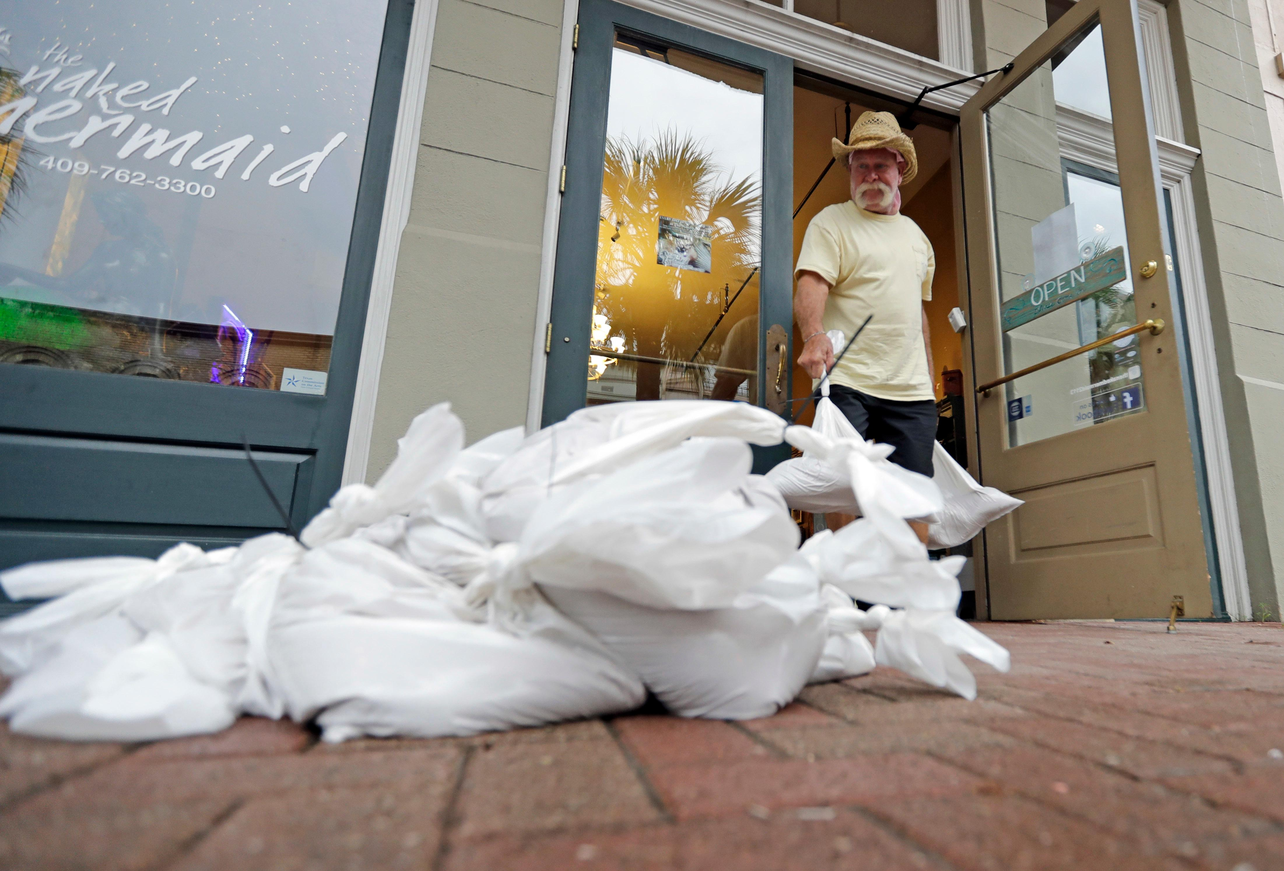 "Lynn Dixon places sandbags outside their home decor store in Galveston, Texas as Hurricane Harvey intensifies in the Gulf of Mexico Friday, Aug. 25, 2017. Conditions were deteriorating along Texas's Gulf Coast on Friday as Hurricane Harvey strengthened and slowly moved toward the state, with forecasters warning that evacuations and preparations ""should be rushed to completion.""  (AP Photo/David J. Phillip)"