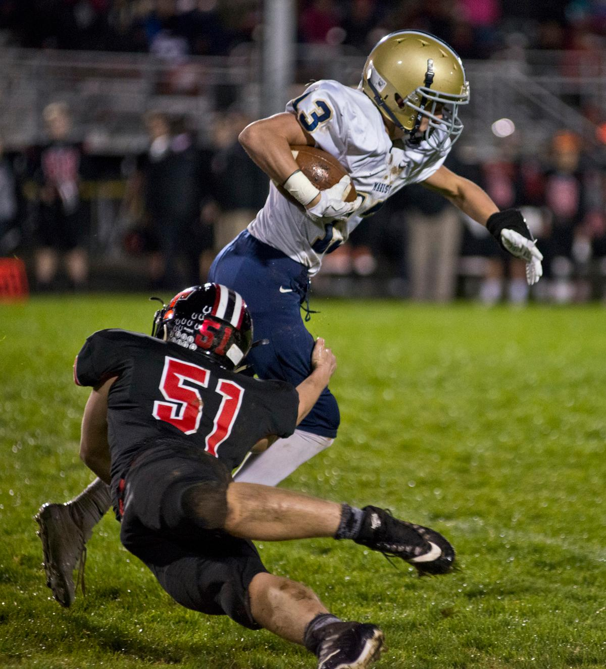 Marist Spartans wide receiver Hagan Stephenson (#13) is tackled by Thurston Colts linebacker Cayden Torkelson (#51). Thurston defeated Marist 50 to 14 to seal the second position in their conference. Photo by Dan Morrison, Oregon News Lab