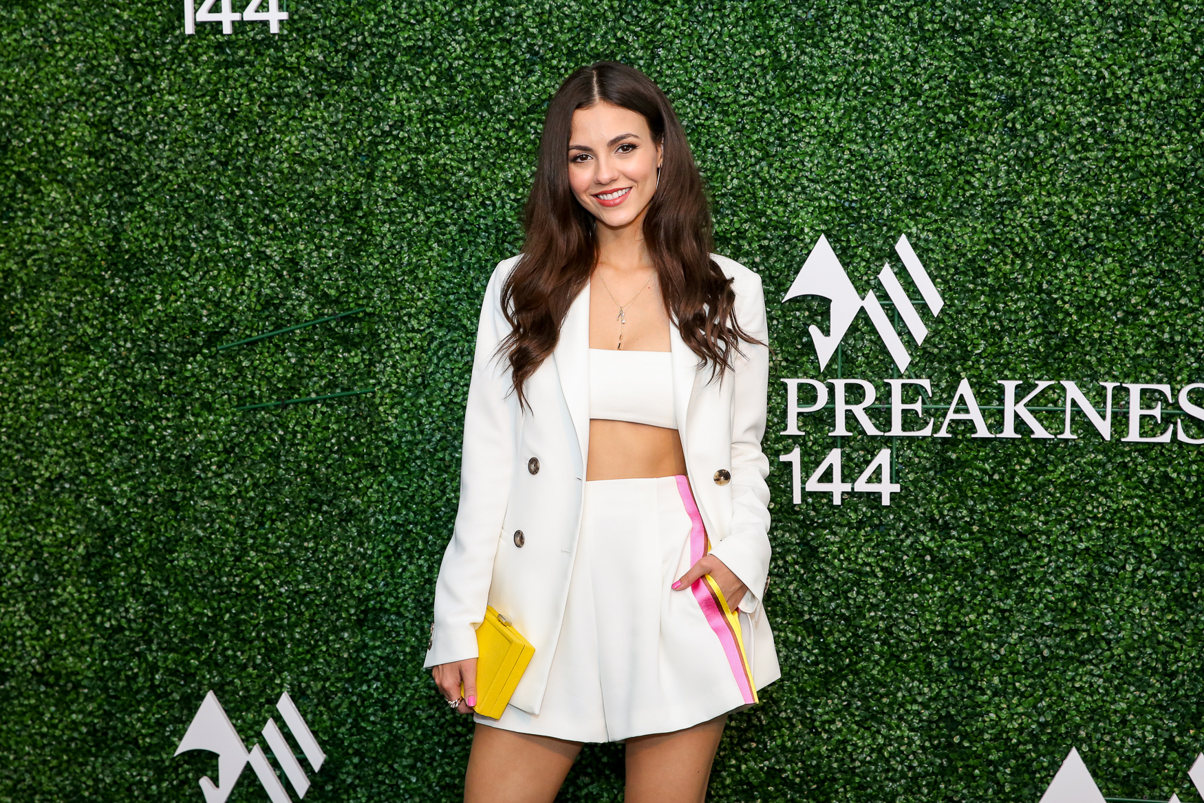 At Preakness, Victoria Justice pumped up the color with a bright yellow clutch in addition to her pink streak.{ }(Amanda Andrade-Rhoades/DC Refined)
