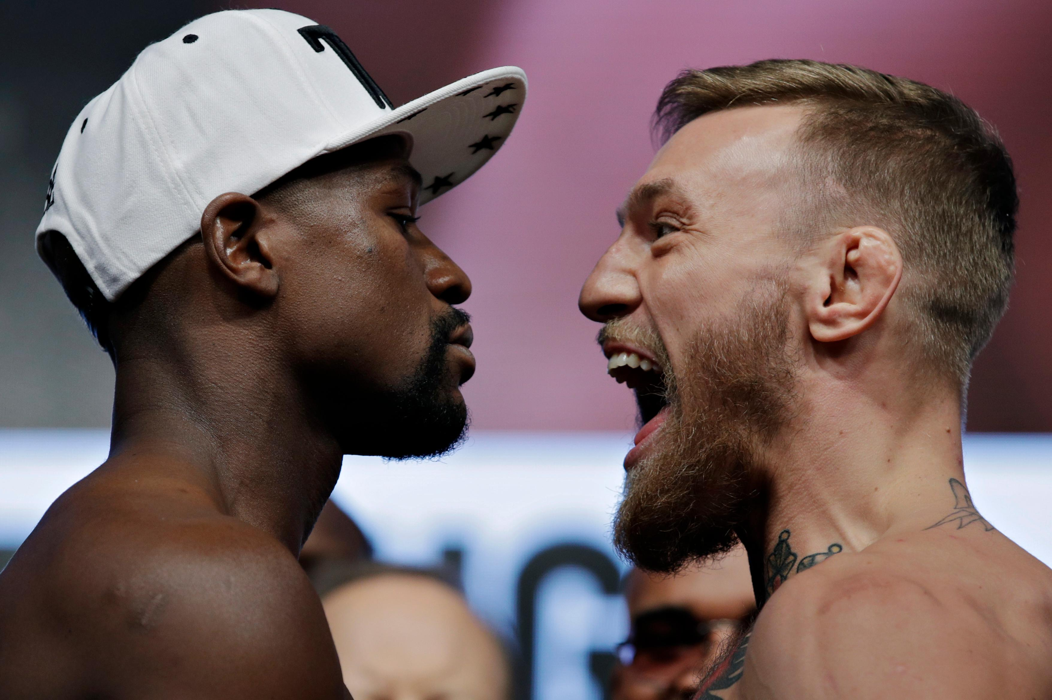 Floyd Mayweather Jr., left, and Conor McGregor face off during weigh-ins Friday, Aug. 25, 2017, in Las Vegas. The two are scheduled to fight in a boxing match Saturday. (AP Photo/John Locher)