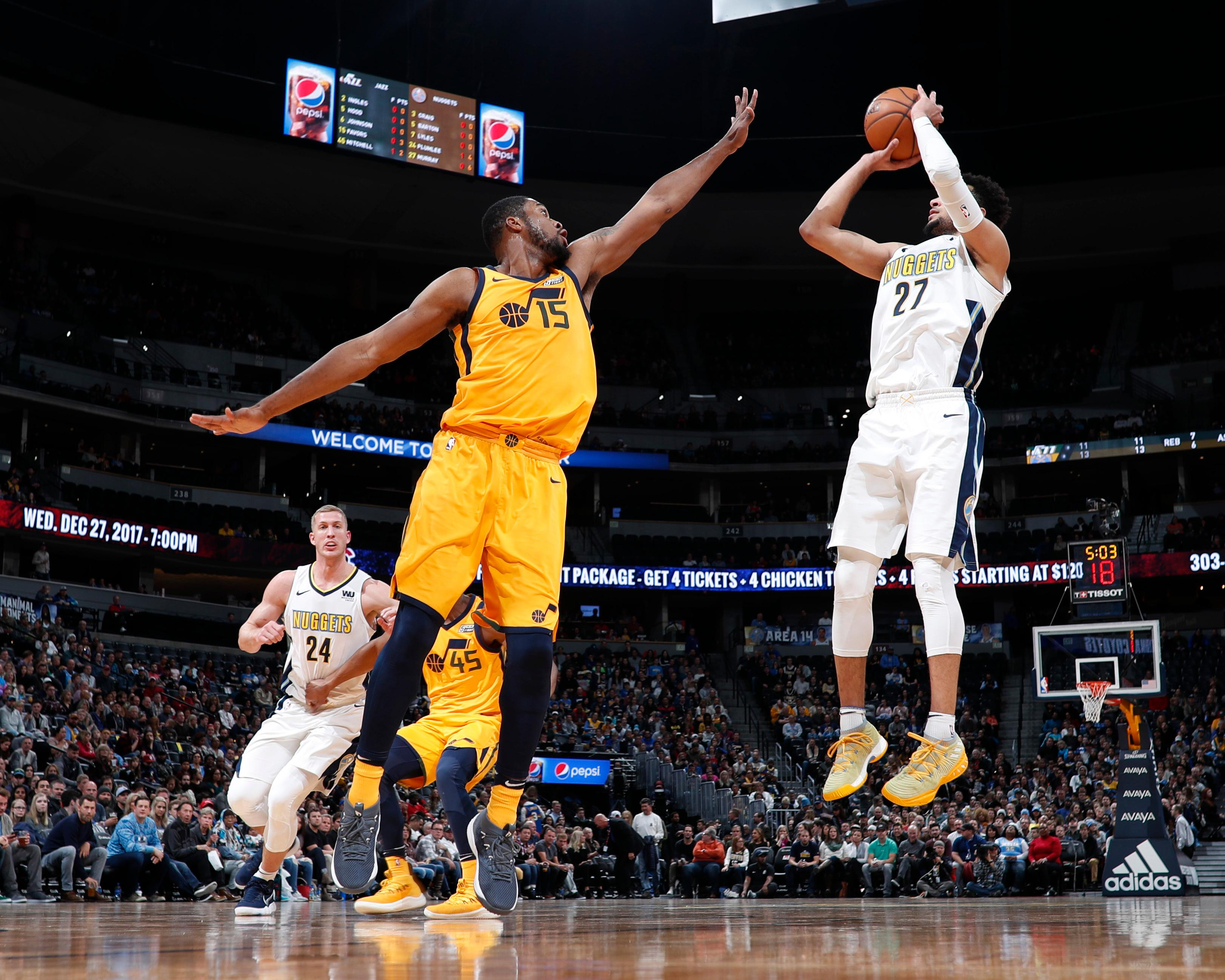 Utah Jazz forward Derrick Favors, left, reaches up to block a shot by Denver Nuggets guard Jamal Murray in the first half of an NBA basketball game, Tuesday, Dec. 26, 2017, in Denver. (AP Photo/David Zalubowski)