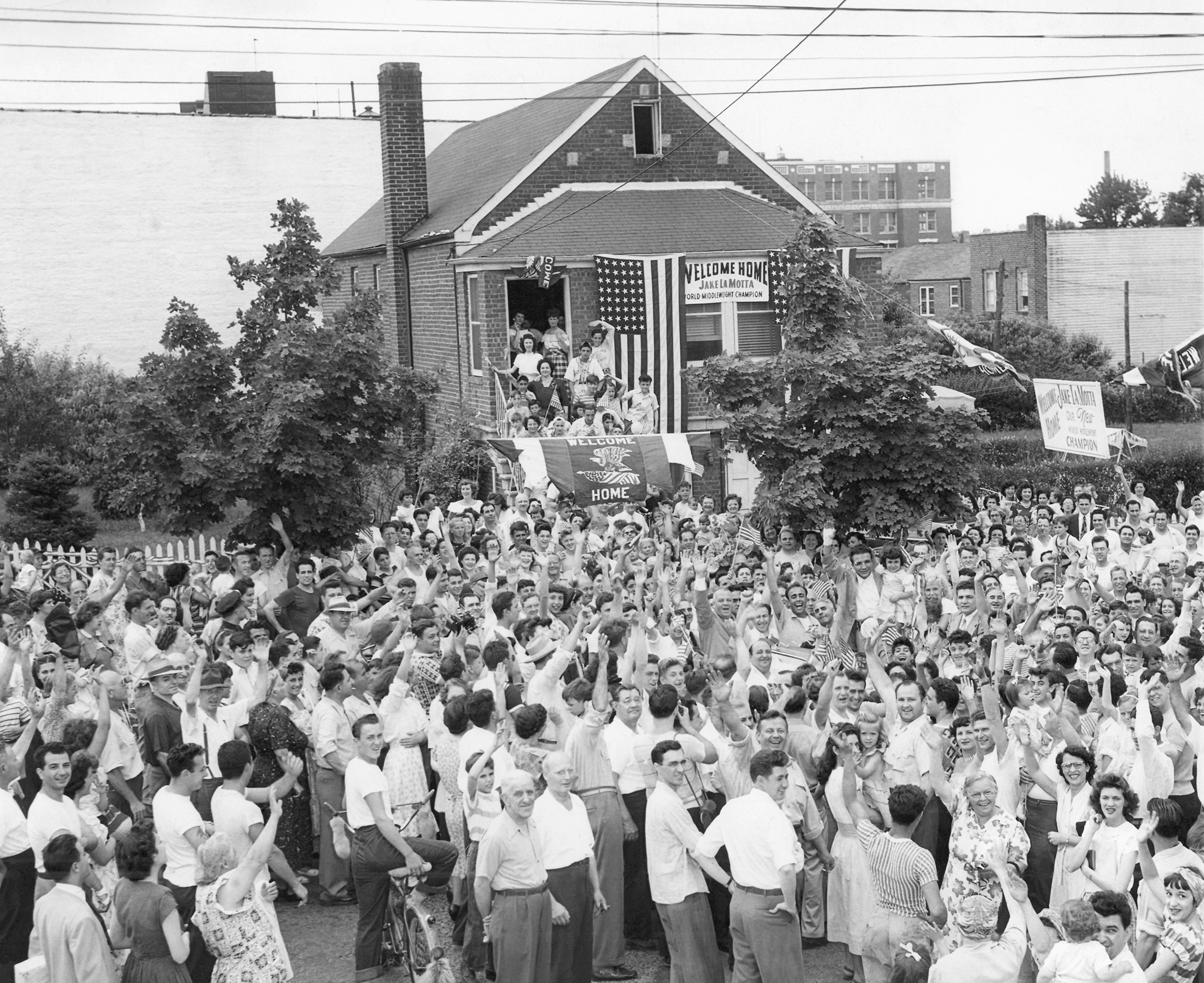 "FILE - In this June 18, 1849, file photo, a crowd gathers in front of Jake Lamotta's home in the Bronx borough of New York, welcoming him home from Detroit, Mich., where he won the middleweight boxing championship against Marcel Cerdan. LaMotta, whose life was depicted in the film ""Raging Bull,"" died Tuesday, Sept. 19, 2017, at a Miami-area hospital from complications of pneumonia. He was 95. (AP Photo/File)"